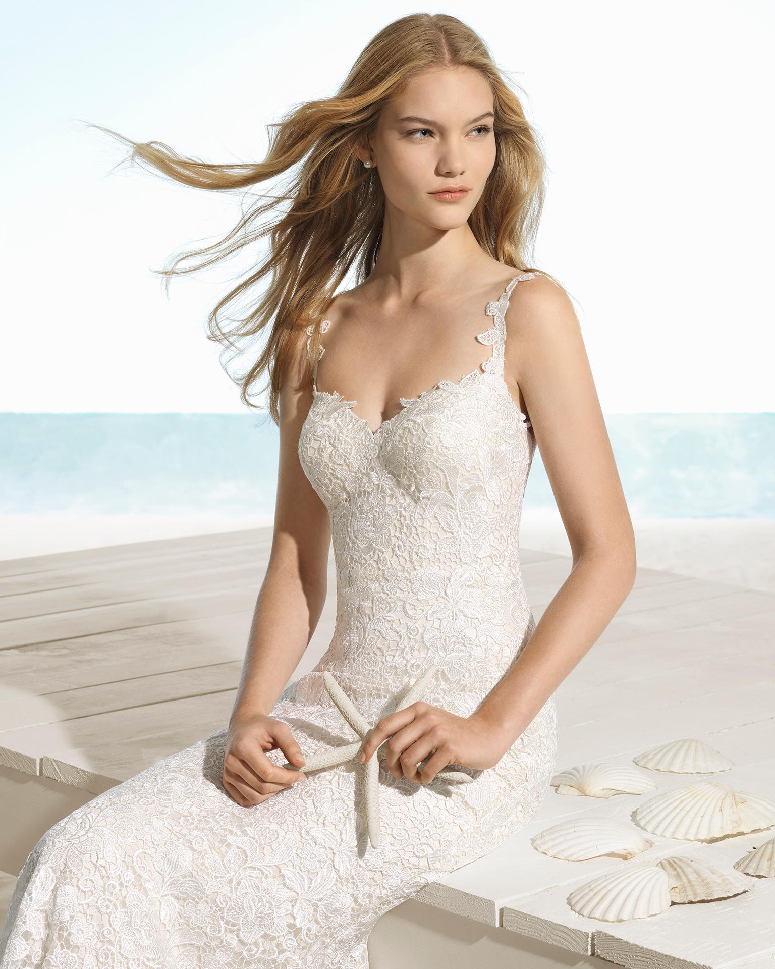 Robe de mariée style sirène en guipure avec col en cœur et décolleté dans le dos, de couleur ivoire.
