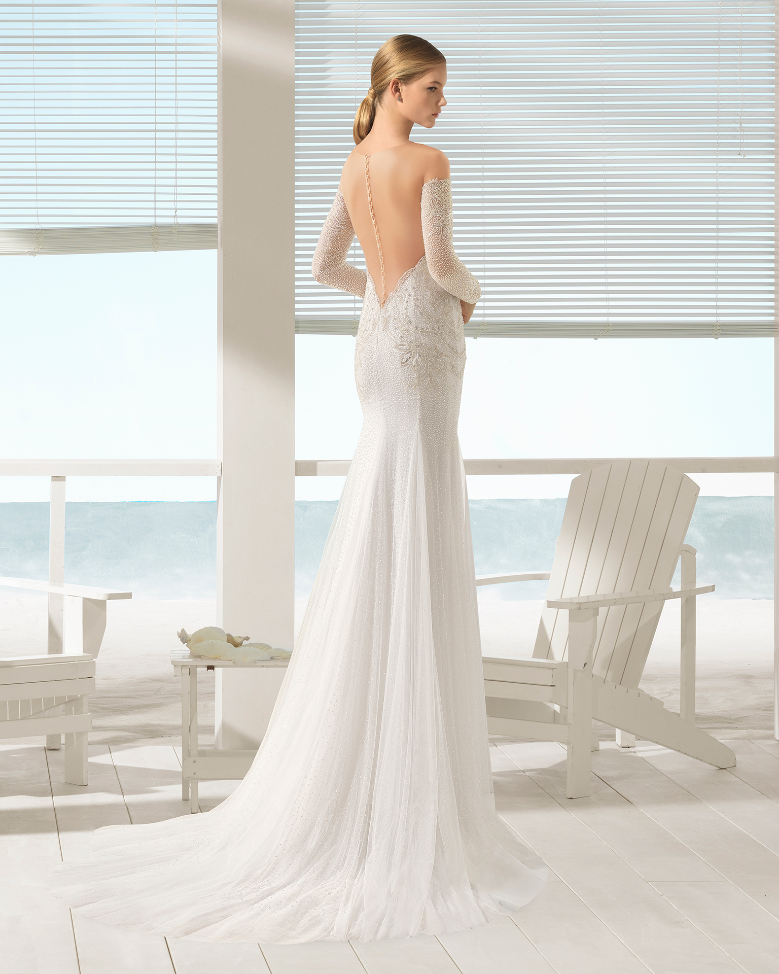 Mermaid-style beaded tulle wedding dress with sweetheart neckline, beaded sleeves and very low back, in natural/nude.
