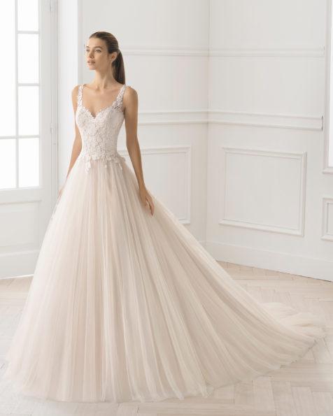 Robe de mariée style trapèze en tulle et guipure avec col en V et décolleté dans le dos, de couleur rose pâle et naturelle.