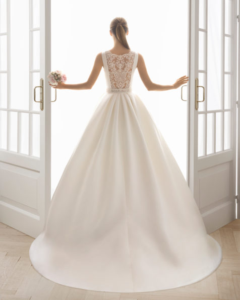Classic-style beaded lace and satin wedding dress with bateau neckline and pockets.