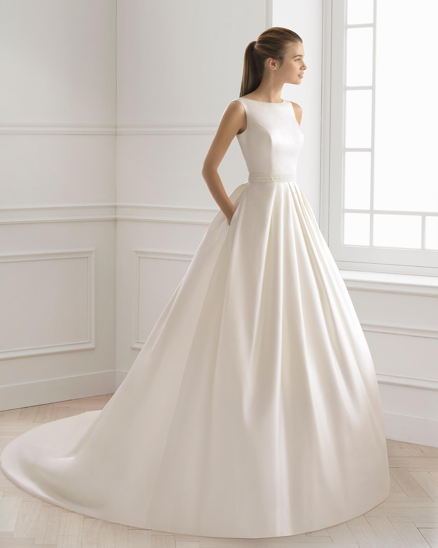Robe de mariée style classique en satin, dentelle et pierreries, avec col bateau et poches.