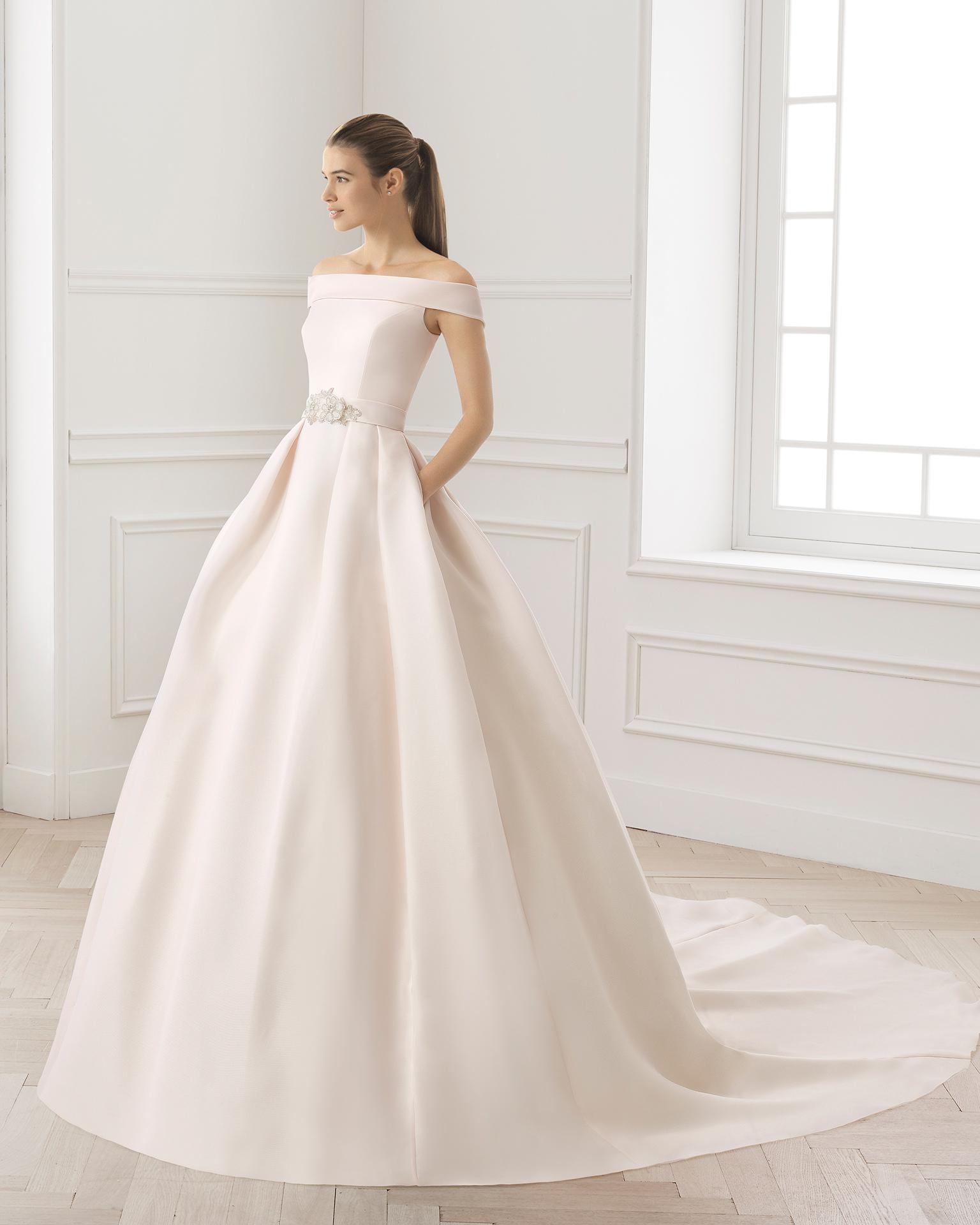 Robe de mariée classique de couture en gazar, avec col bateau et découpe à la taille, de couleur rose et naturelle.