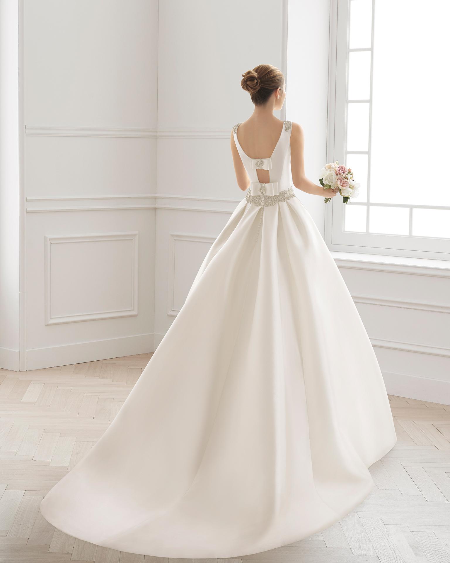Vestido de novia clásico de costura de mikado, con escote barco y espalda cerrada con lazos, y cinturón de pedrería en cintura, en color natural.