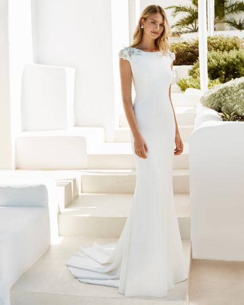 Vestido de noiva estilo sereia de crepe com decote tipo barco e costas decotadas, com aplicações de flores com cristais em cor natural e em cor natural/rosé.