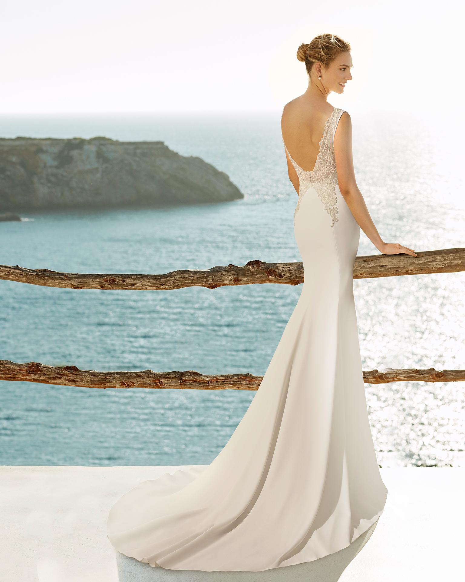Vestido de noiva estilo sereia de crepe e costas decotadas, com adorno de brilhantes.
