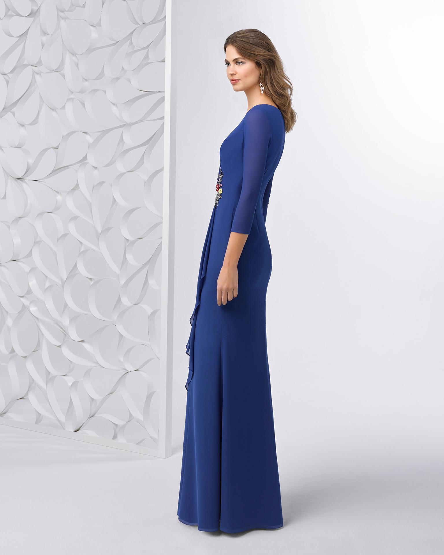 Rochie de cocktail lungă din voal cu strasuri, cu spatele cu efect de bijuterie. Disponibilă în culorile roșu și albastru. Colecția FIESTA AIRE BARCELONA 2018.
