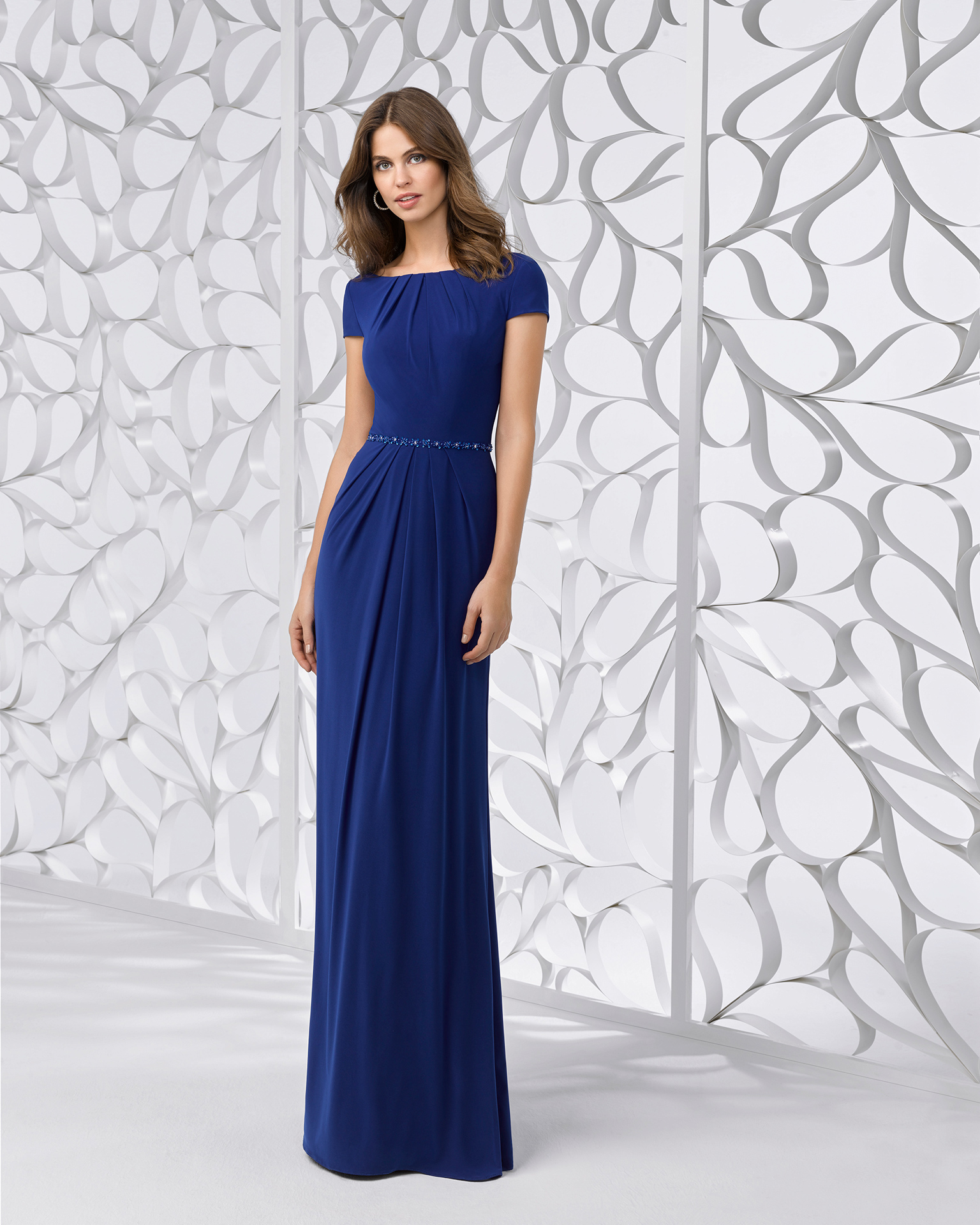 Stretch crepe cocktail dress with short sleeves, bateau neckline, cape back, gathered bodice and skirt and beaded belt. Available in cobalt, silver and red. 2018 FIESTA AIRE BARCELONA Collection.