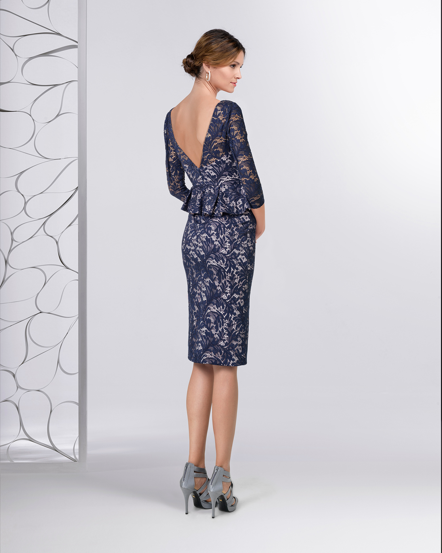 Short lace cocktail dress with peplum and three-quarter sleeves. Available in navy blue/pink. 2018 FIESTA AIRE BARCELONA Collection.
