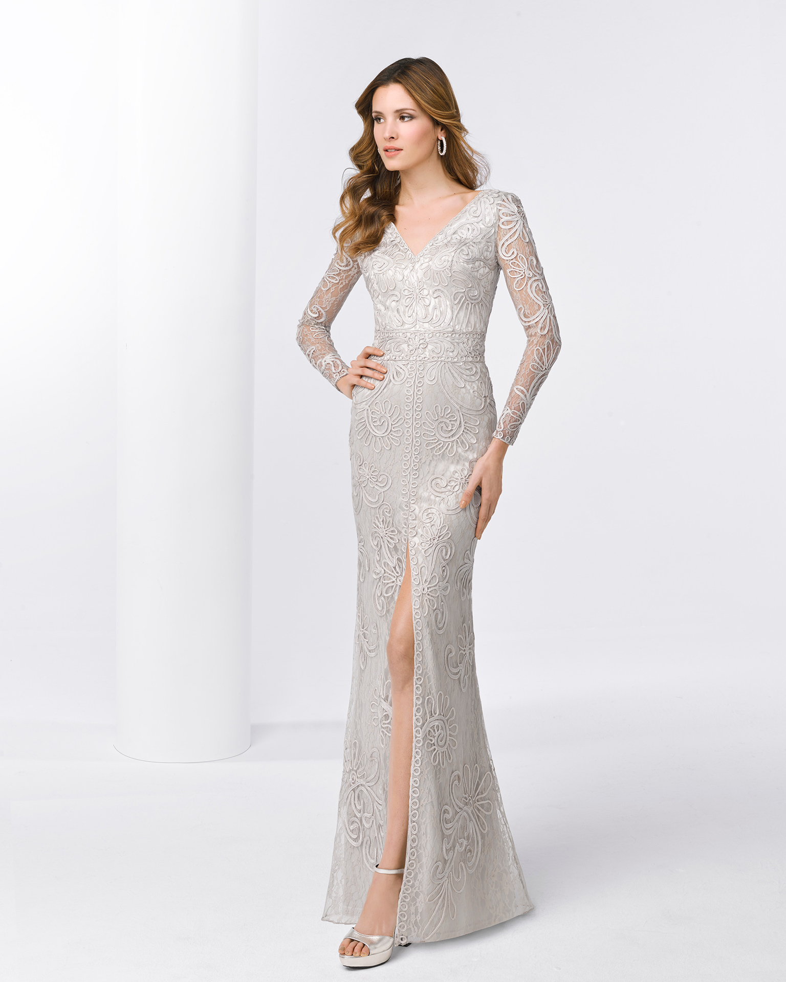 Long lace cocktail dress with long sleeves and slit front. Available in silver and cobalt. 2018 FIESTA AIRE BARCELONA Collection.