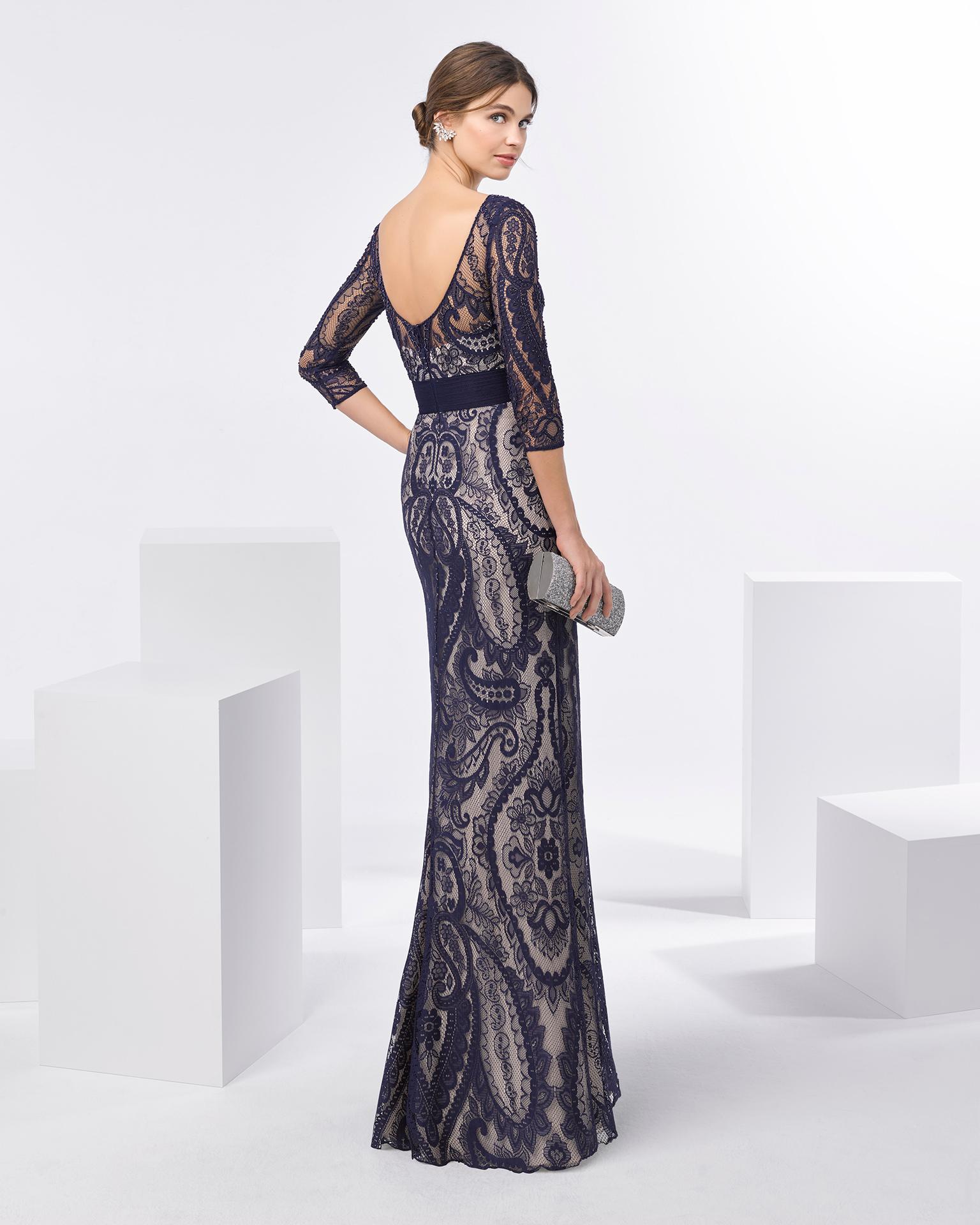 Rochie de cocktail lungă din dantelă cu strasuri, cu decolteu în V și mânecă trei sferturi. Disponibilă în culorile bleumarin, negru/nude și argintiu. Colecția FIESTA AIRE BARCELONA 2018.