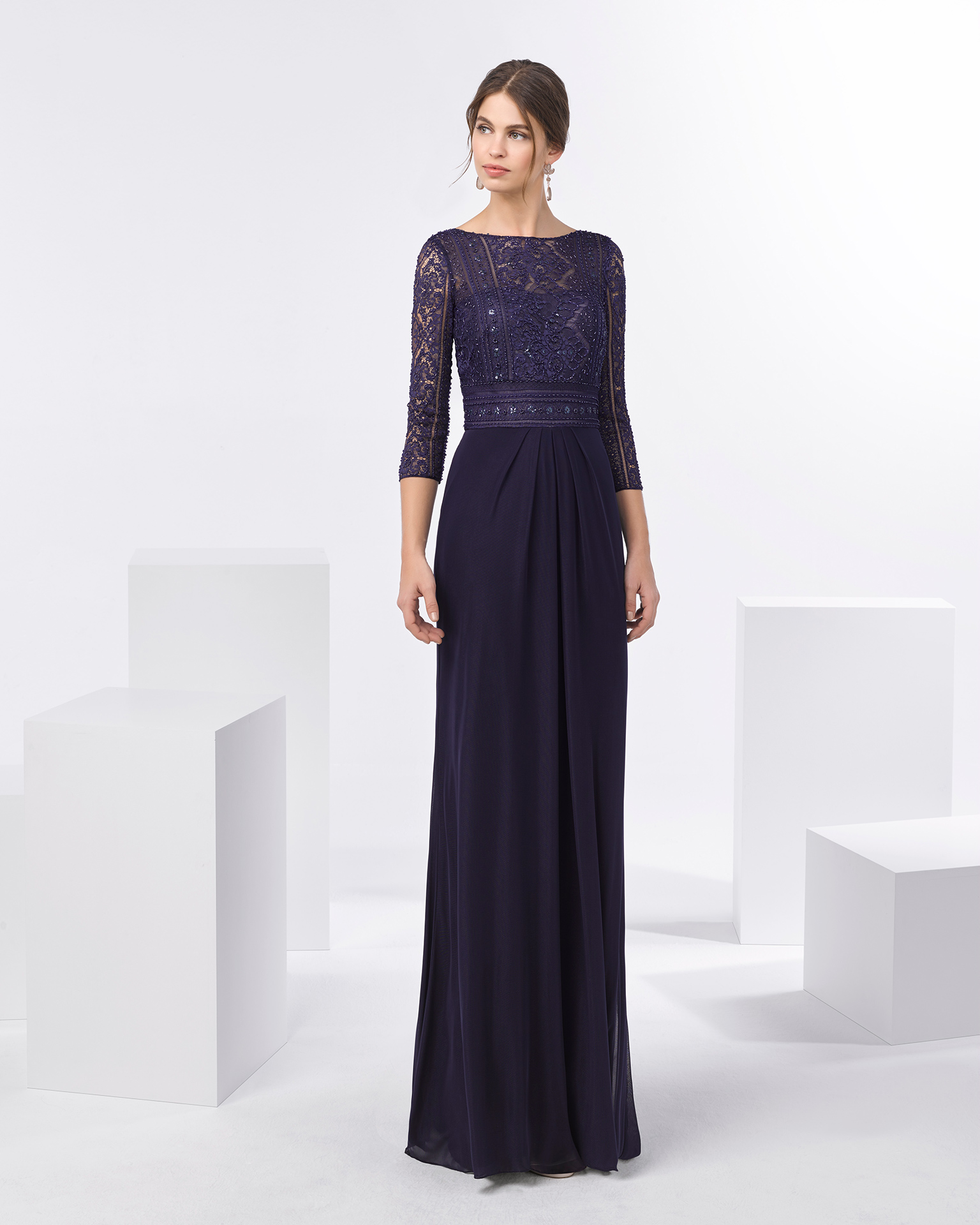 Long cocktail dress with beaded lace bodice, three-quarter sleeves and stretch tulle skirt. Available in smoke and navy blue/nude. 2018 FIESTA AIRE BARCELONA Collection.