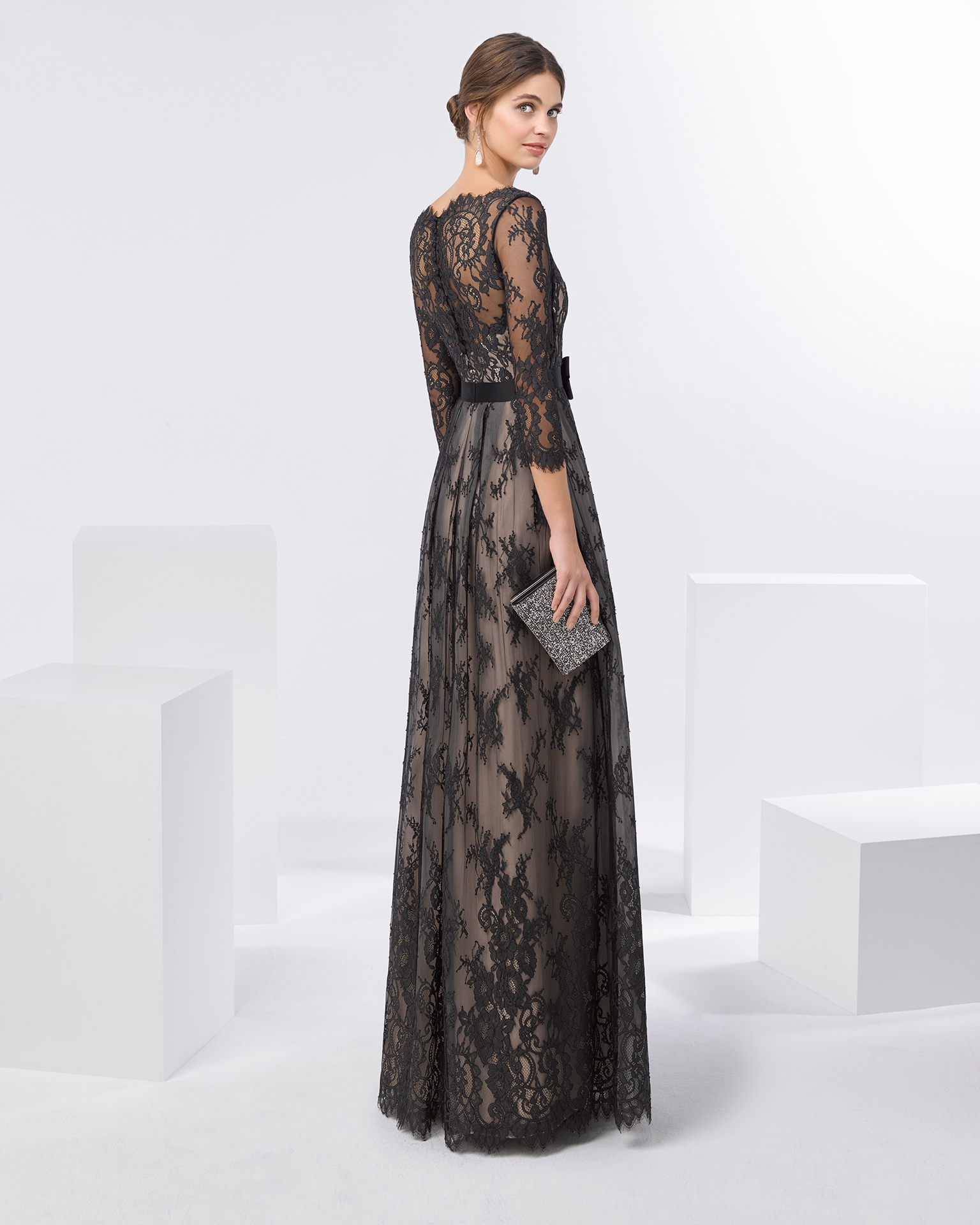 Long lace cocktail dress with bow on waist, V-neckline and three-quarter sleeves. Available in silver/nude, black/nude and navy blue/nude. 2018 FIESTA AIRE BARCELONA Collection.