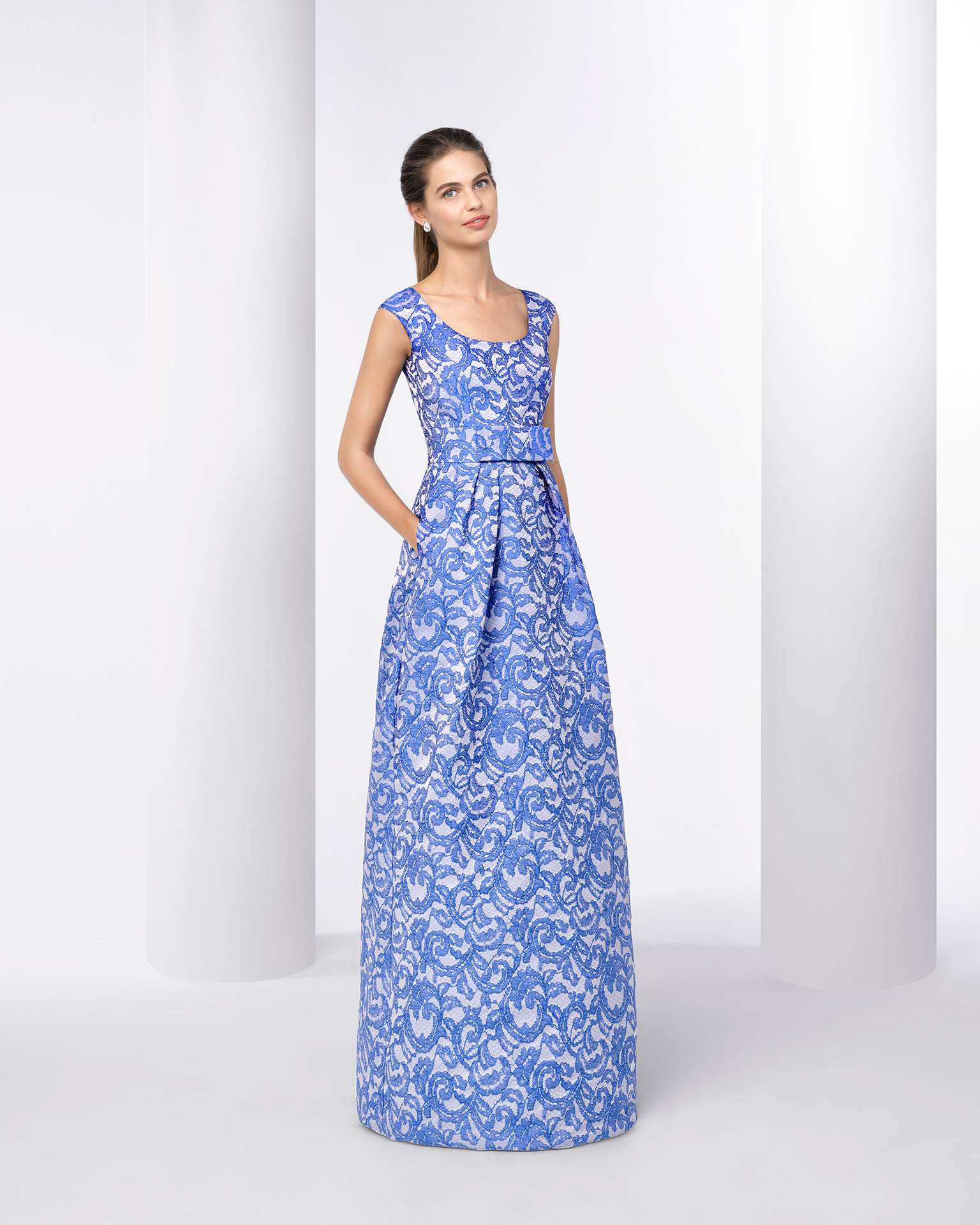 Long brocade cocktail dress with round neckline, structured full skirt with pockets and detail on waist. Available in blue and pink. 2018 FIESTA AIRE BARCELONA Collection.