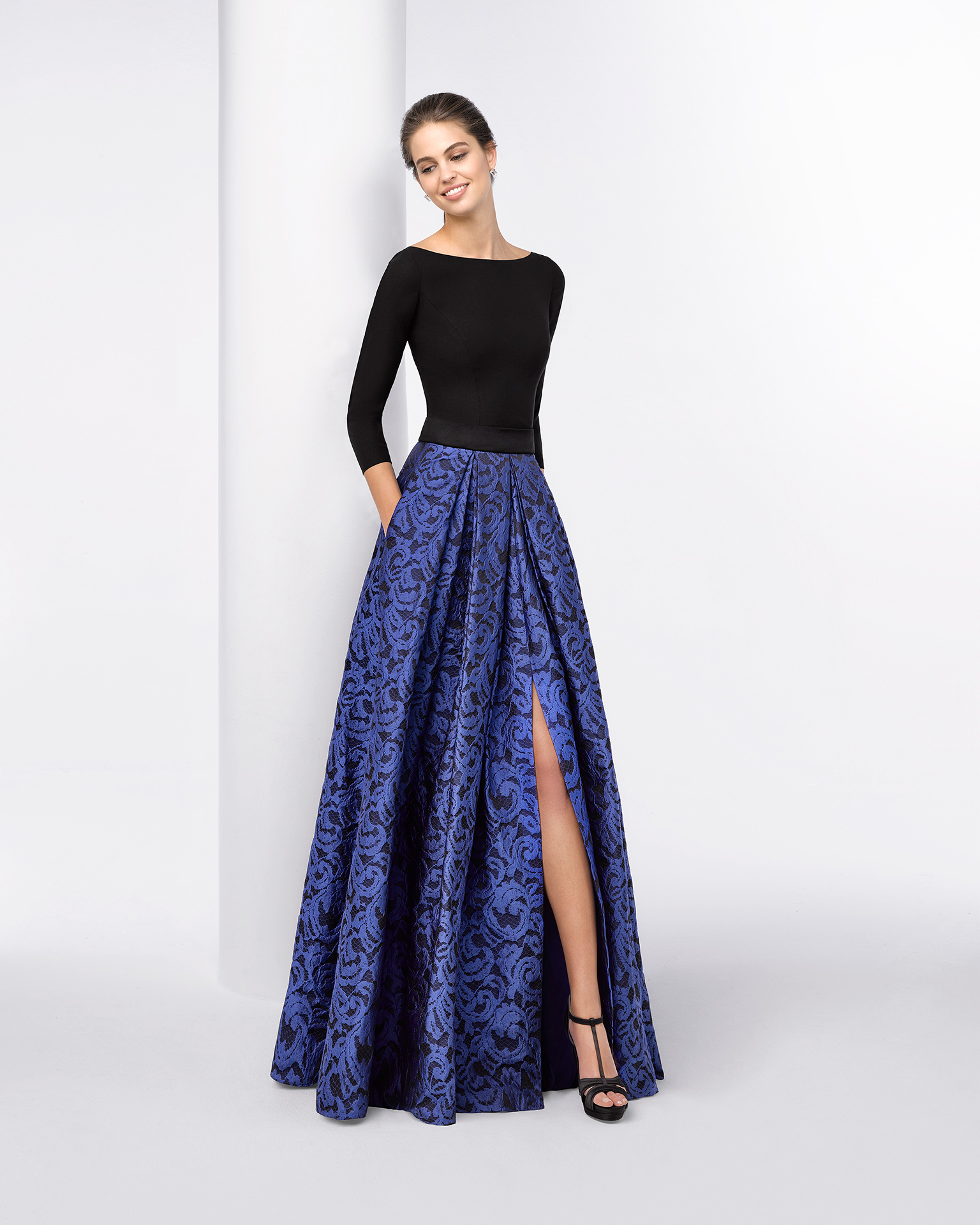 Long cocktail dress with rigid bodice, three-quarter sleeves and structured full brocade skirt with slit front. Available in cobalt/black. 2018 FIESTA AIRE BARCELONA Collection.