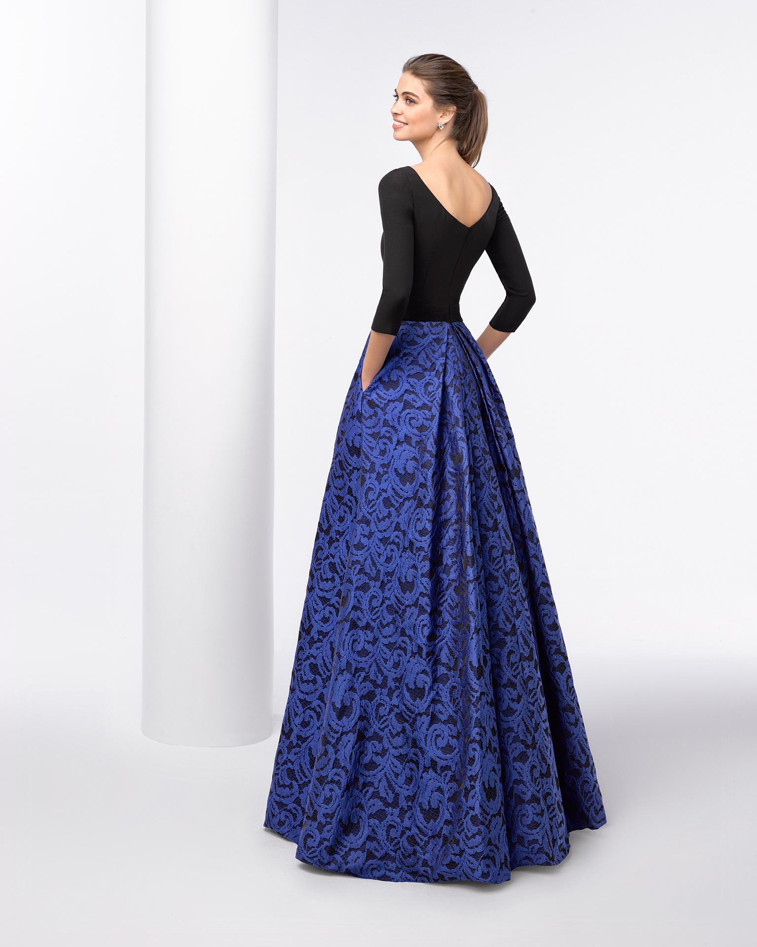 Rochie de cocktail lungă cu corsaj rigid, mânecă trei sferturi și fustă plină structurată din brocart cu despicătură în față. Disponibilă în culoarea cobalt/negru. Colecția FIESTA AIRE BARCELONA 2018.