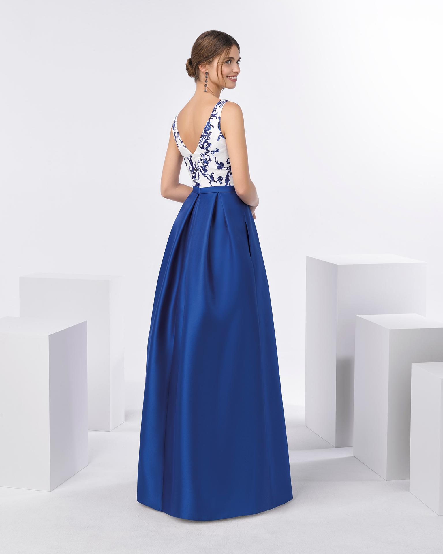 长款鸡尾酒会礼服,配V领锦缎紧身上衣和带口袋的结构感米卡多伞裙。有深蓝色可选。 FIESTA AIRE BARCELONA 新品系列 2018.