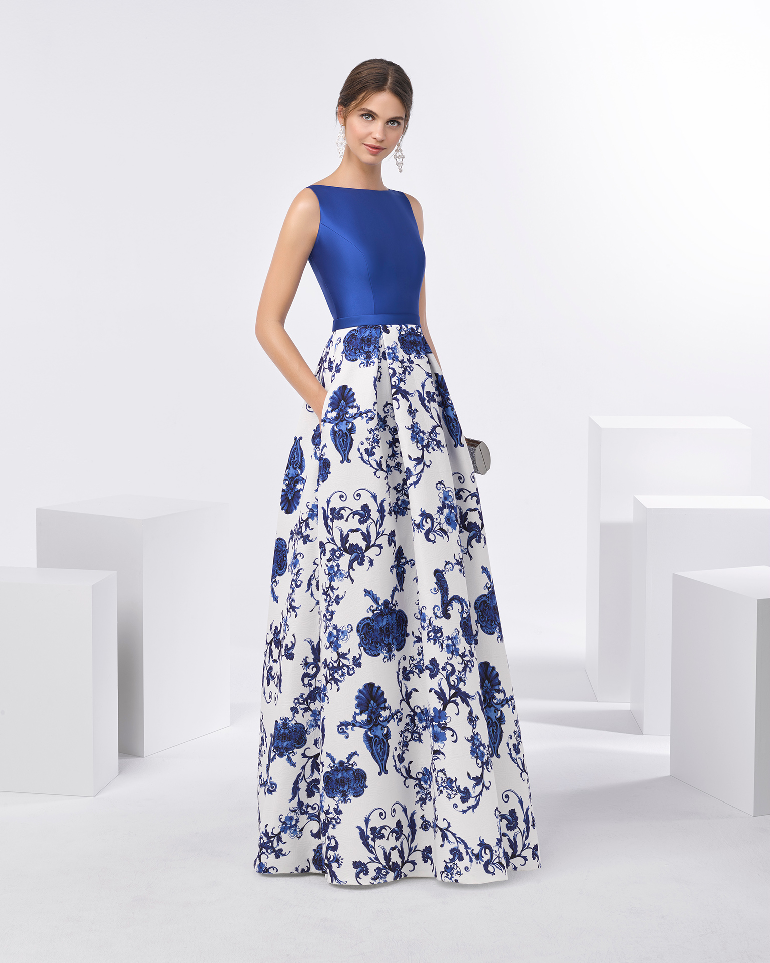 Long cocktail dress with mikado bodice, back neckline with bow detail and structured full brocade skirt with pockets. Available in cobalt. 2018 FIESTA AIRE BARCELONA Collection.