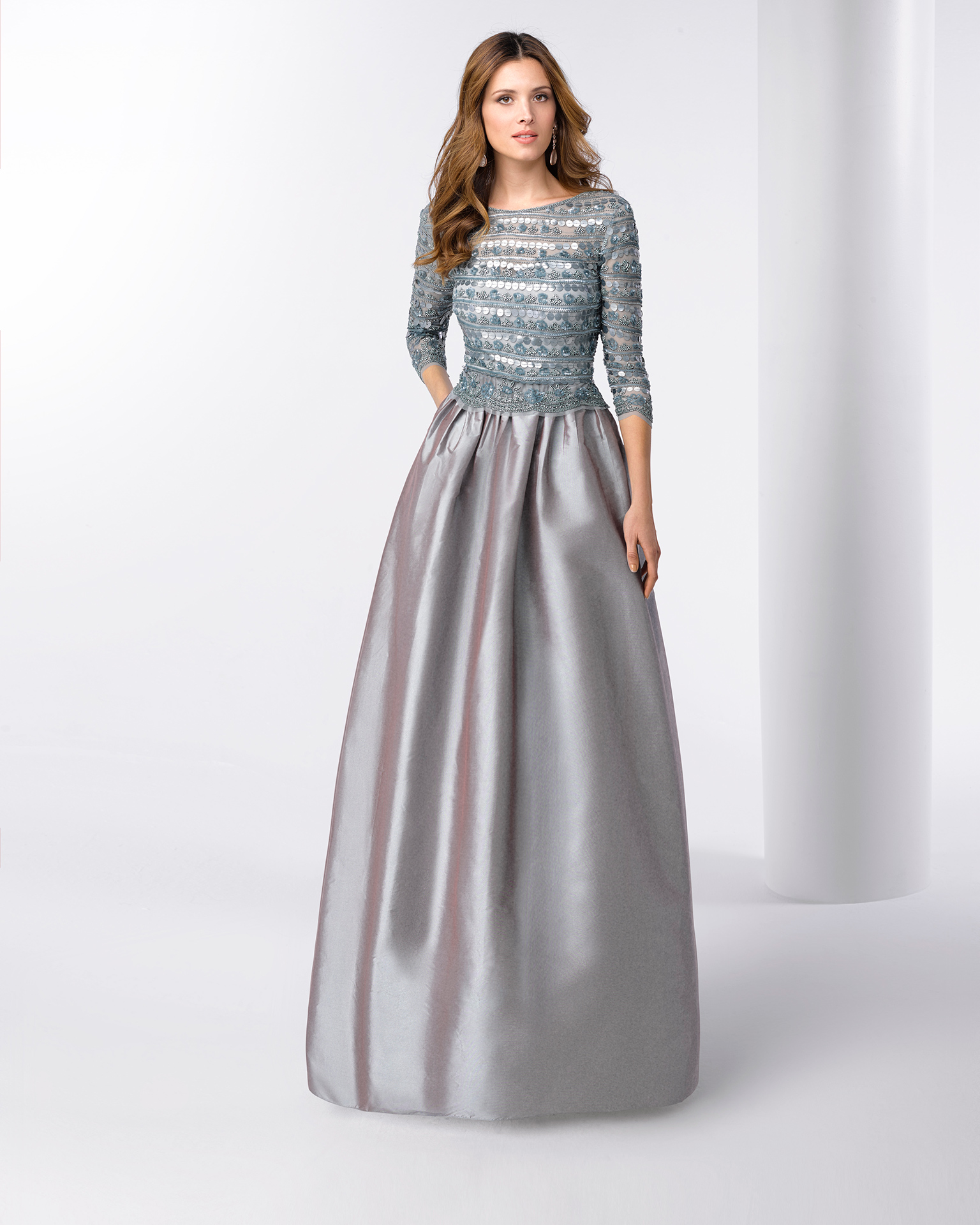 Robe de soirée longue en taffetas avec corsage en pierreries à manches 3/4. Disponible en vert, argent et bleu marine. Collection FIESTA AIRE BARCELONA 2018.