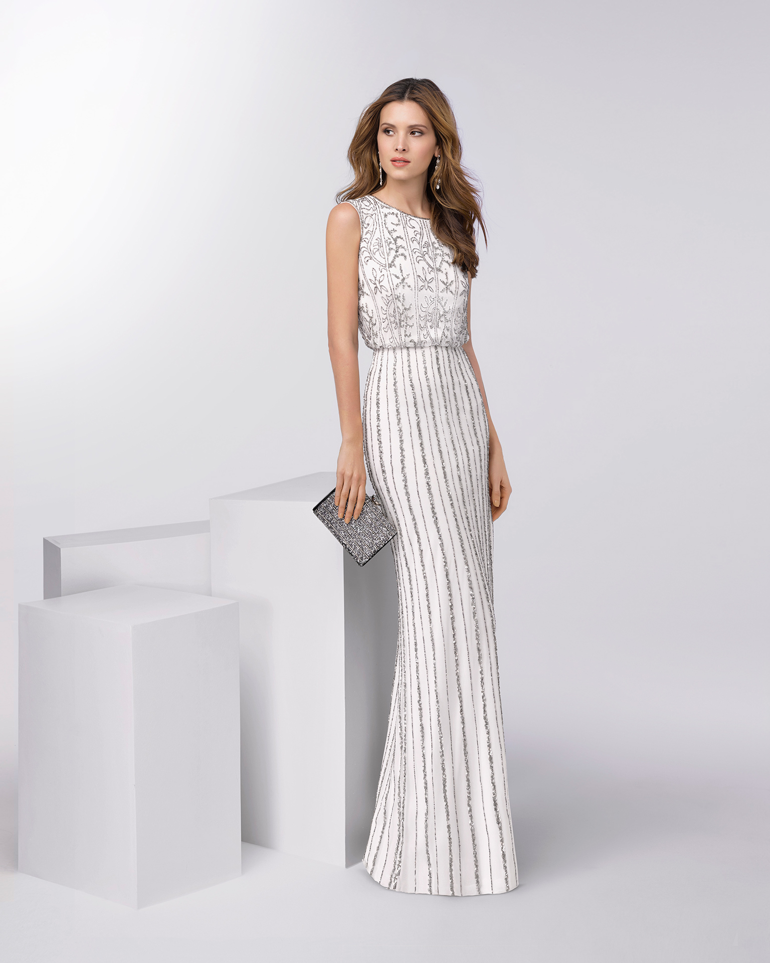 Long sleeveless beaded cocktail dress. Available in silver/ivory. 2018 FIESTA AIRE BARCELONA Collection.
