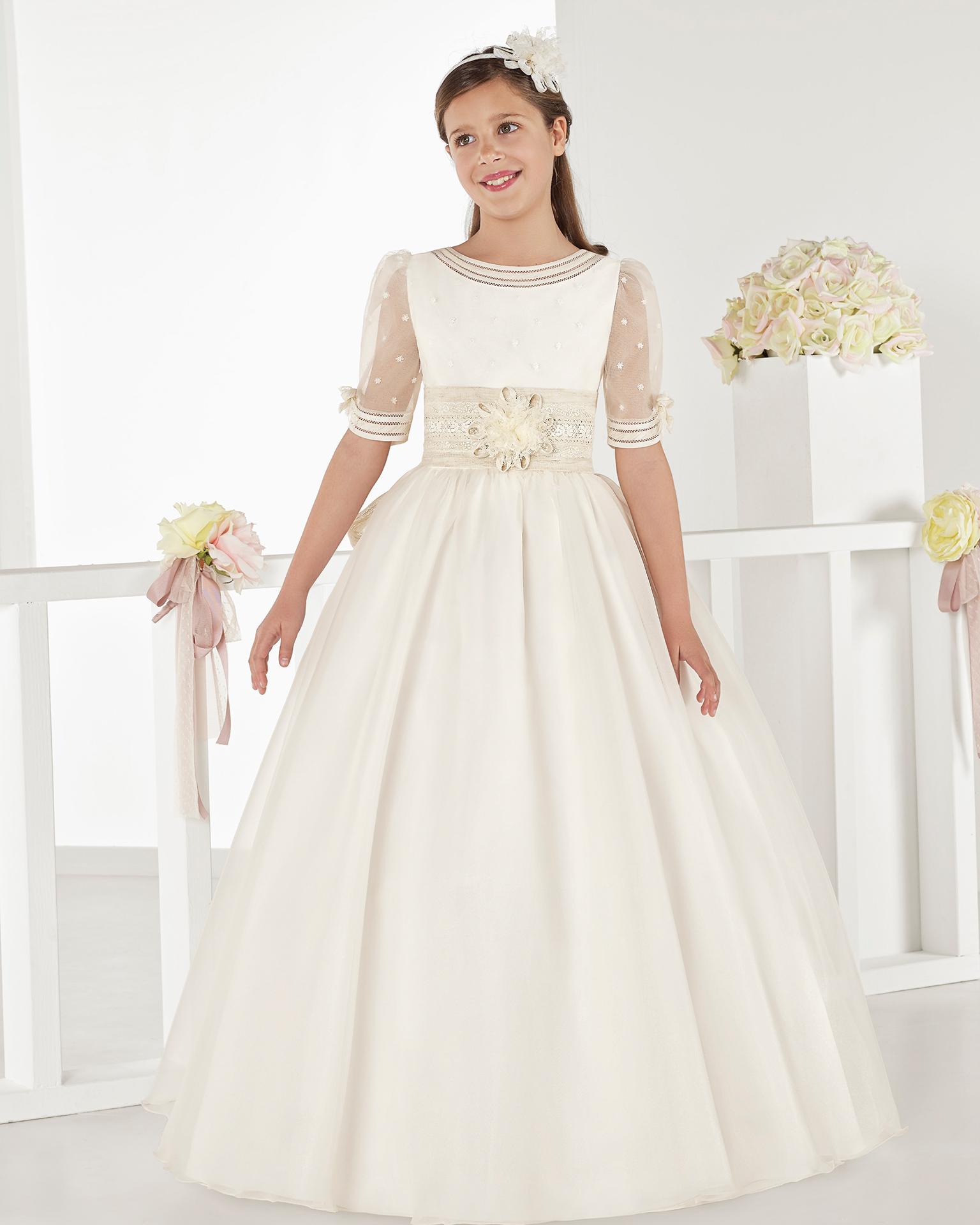 Vestido de comunhão fantasia, de cintura standard, de organza baça, em cor marfim. Coleção AIRE COMUNION 2018.