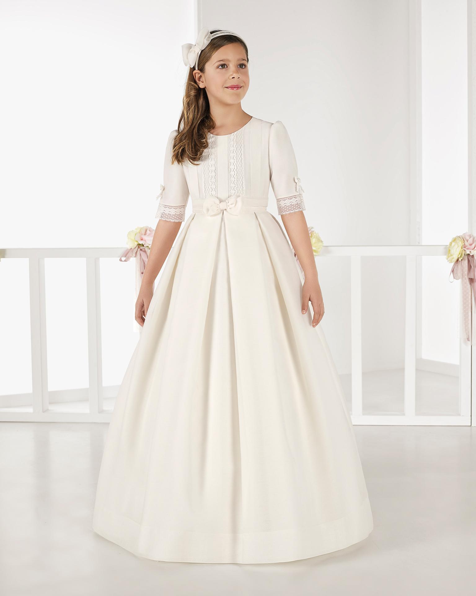 Vestido de comunhão clássico listrado, de corte império, em cor marfim. Coleção AIRE COMUNION 2018.