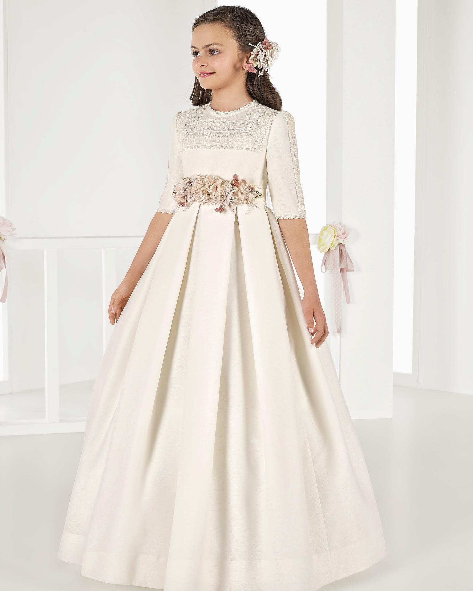 Vestido de comunhão romântico, de corte império de brocado, em cor marfim. Coleção AIRE COMUNION 2018.