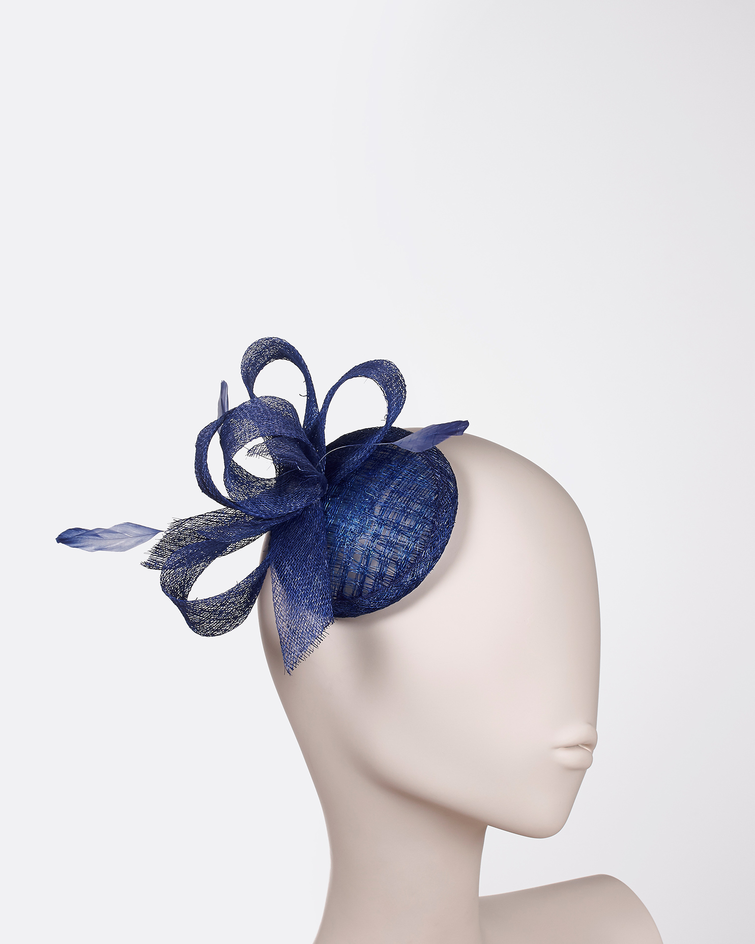 Sinamay headpiece with feather detail. Available in black, navy blue, cobalt, blue, silver, nude, red, coral, fuchsia and yellow. 2018 FIESTA AIRE BARCELONA Collection.