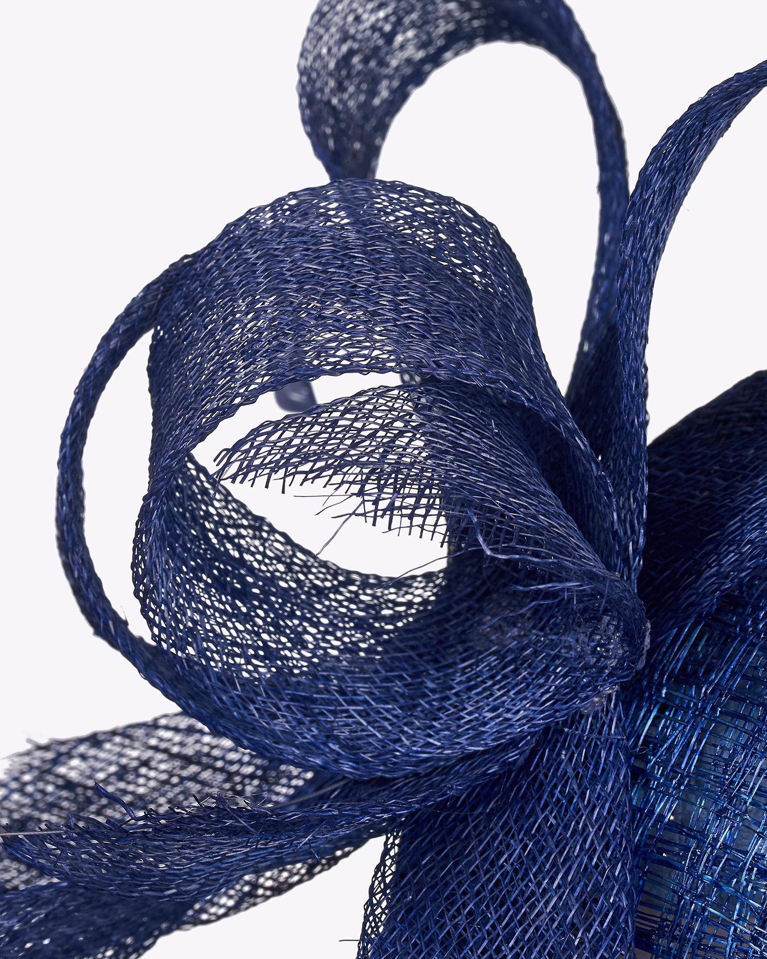 Acconciatura di sinamay con decorazione di piuma. Disponibile in colore nero, blu marino, cobalto, blu, argento, nude, rosso, corallo, fucsia e giallo. Collezione FIESTA AIRE BARCELONA 2018.