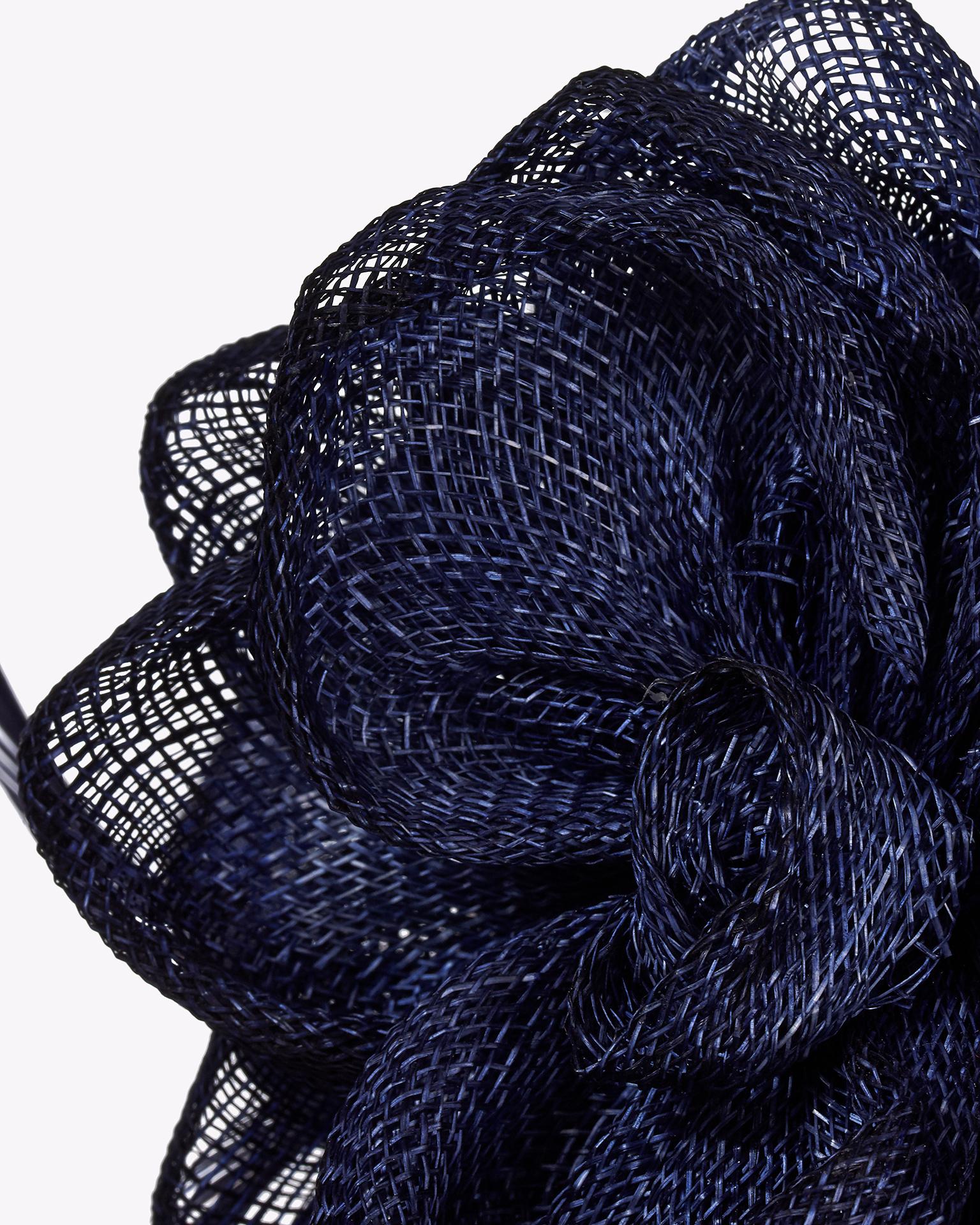 Toucado de sinamay com adorno de pluma. Disponível em preto, azul-marinho, azul-cobalto, azul, prateado, cor de pele, vermelho, coral fúcsia e amarelo. Coleção FIESTA AIRE BARCELONA 2018.