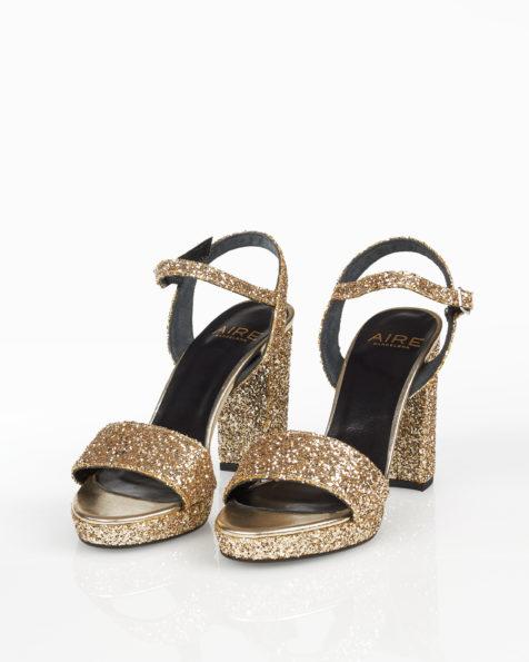 Cocktail-Sandalette mit Glitter-Effekt, Plateau und hohem Absatz, erhältlich in Schwarz, Bleigrau, Marineblau, Silber und Champagner. Kollektion FIESTA AIRE BARCELONA 2018.