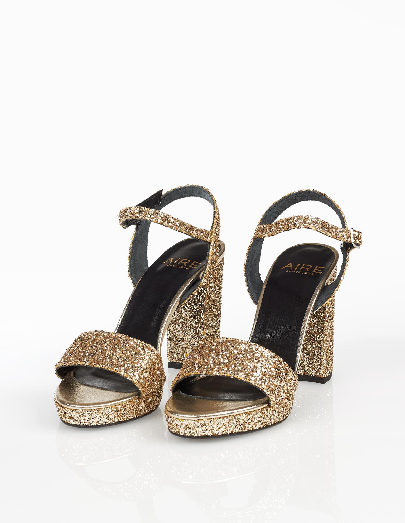 Sandálias de cocktail de glitter com plataforma e salto alto, disponíveis em preto, cor de chumbo, azul-marinho, prateado e champanhe. Coleção FIESTA AIRE BARCELONA 2018.