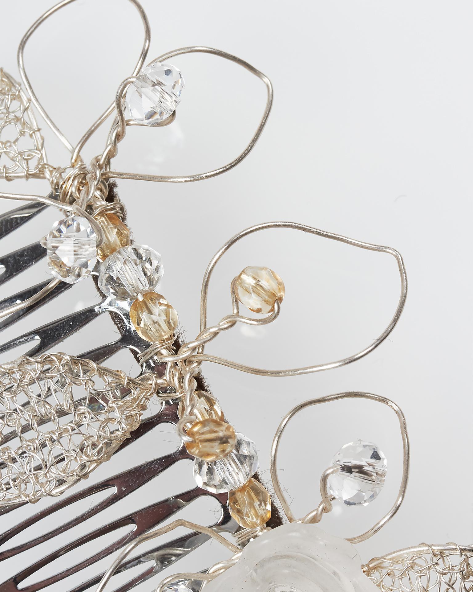 .2018 مجموعة فساتين AIRE BARCELONA طَرحة مشطيّة Lia مسلّكة باللون الفضي، ذات تصميم على شكل وريقات مرصّعة بالجواهر، ومزيّنة بالكريستال، باللون الفضي.