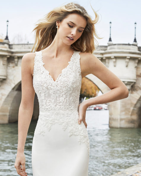 Sheath-style wedding dress in beaded lace and crepe Georgette. V-neckline with chiffon and lace cape and low back. Available in natural. 2019 AIRE BARCELONA Collection.