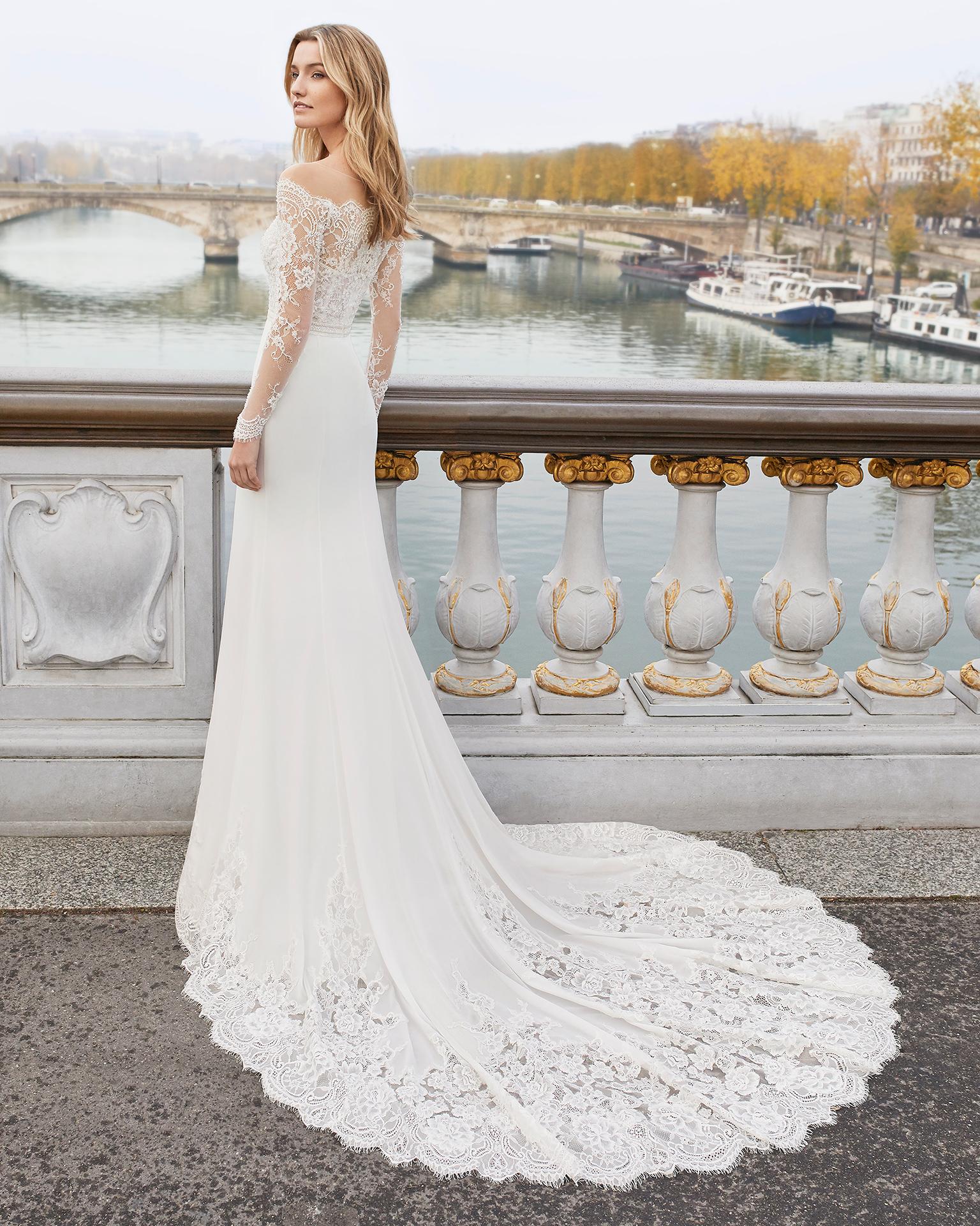 Vestido de novia corte recto de encaje, georgette y pedrería. Escote barco, manga larga. Disponible en color natural. Colección AIRE BARCELONA 2019.