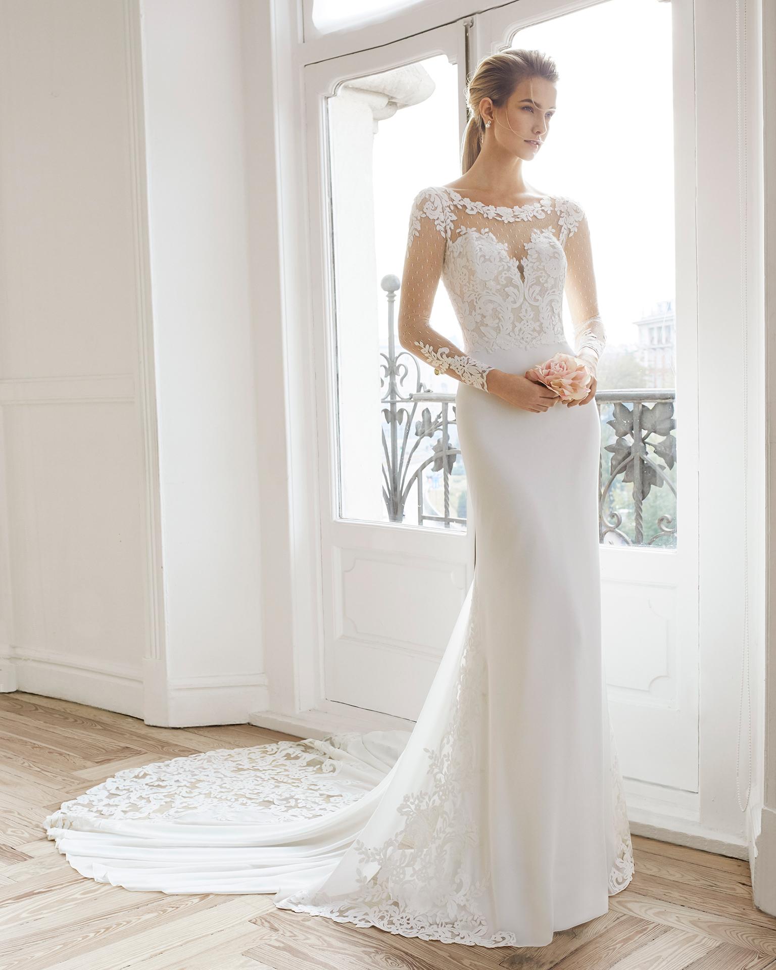 Vestido de novia corte recto en georgette y encaje. Escote barco de manga larga y espalda escotada. Disponible en color natural. Colección AIRE BARCELONA 2019.