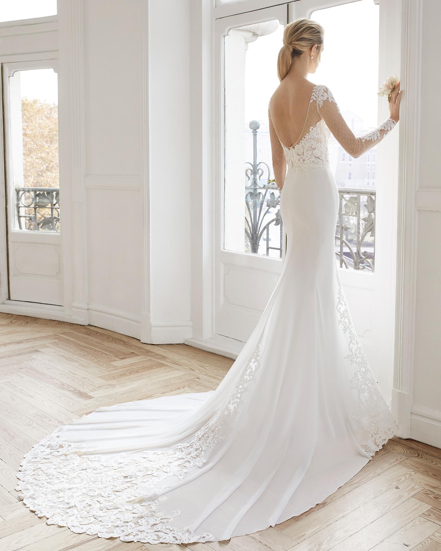Vestido de noiva corte reto de crepe georgete e renda. Decote à barco, de manga comprida e costas decotadas. Disponível em cor natural. Coleção AIRE BARCELONA 2019.