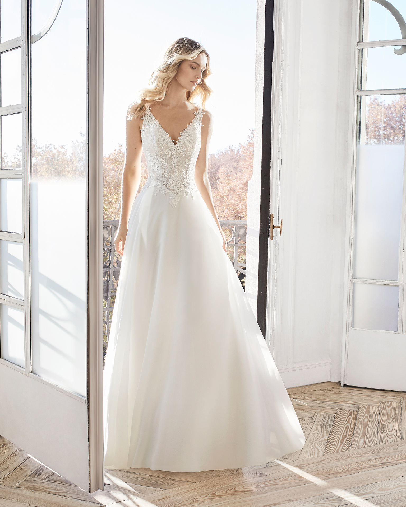 A-line lace and chiffon wedding dress. V-neckline and low back. Available in natural. 2019 AIRE BARCELONA Collection.