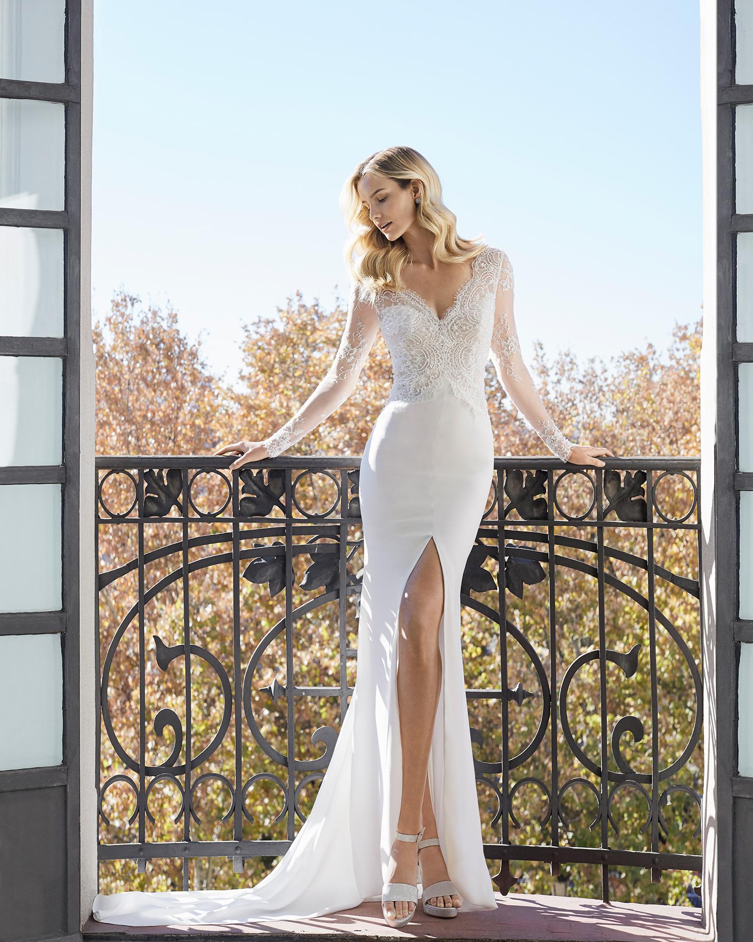 Vestido de noiva corte reto de crepe, renda e brilhantes. Decote em V, manga comprida e costas em V. Coleção AIRE BARCELONA 2019.