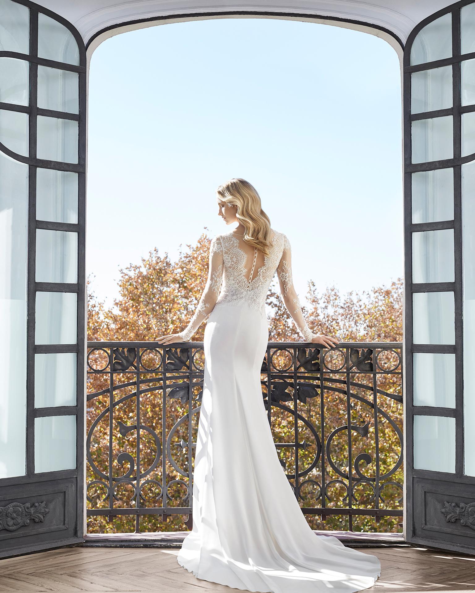 Vestido de novia corte recto en crepe, encaje y pedrería. Escote V, manga larga y espalda V. Disponible en color natural. Colección AIRE BARCELONA 2019.