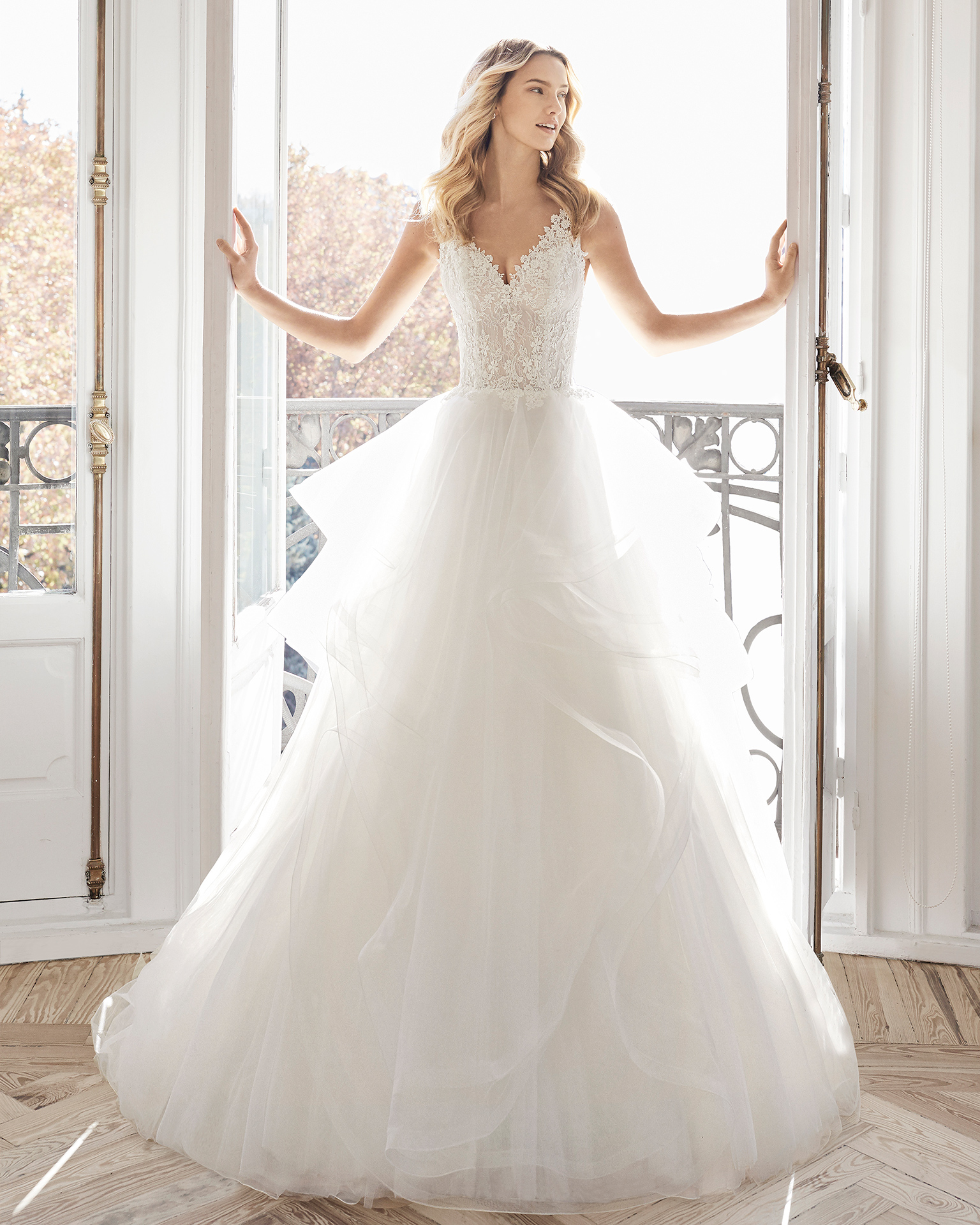 Princess-style wedding dress in lace with tulle flounces. V-neckline and back. Available in natural. 2019 AIRE BARCELONA Collection.
