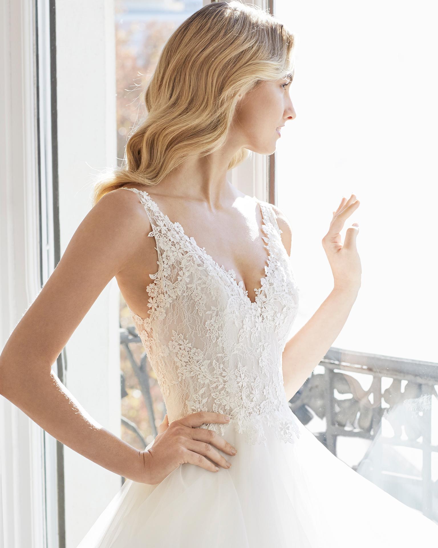 Vestido de novia estilo princesa de encaje y volantes de tul. Escote en V y espalda en V. Disponible en color natural. Colección AIRE BARCELONA 2019.