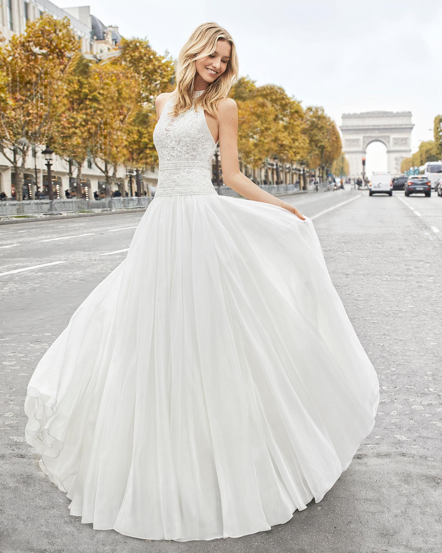 Robe de mariée style trapèze en voile, dentelle et pierreries. Col halter et dos nu. Disponible en couleur naturelle. Collection AIRE BARCELONA 2019.