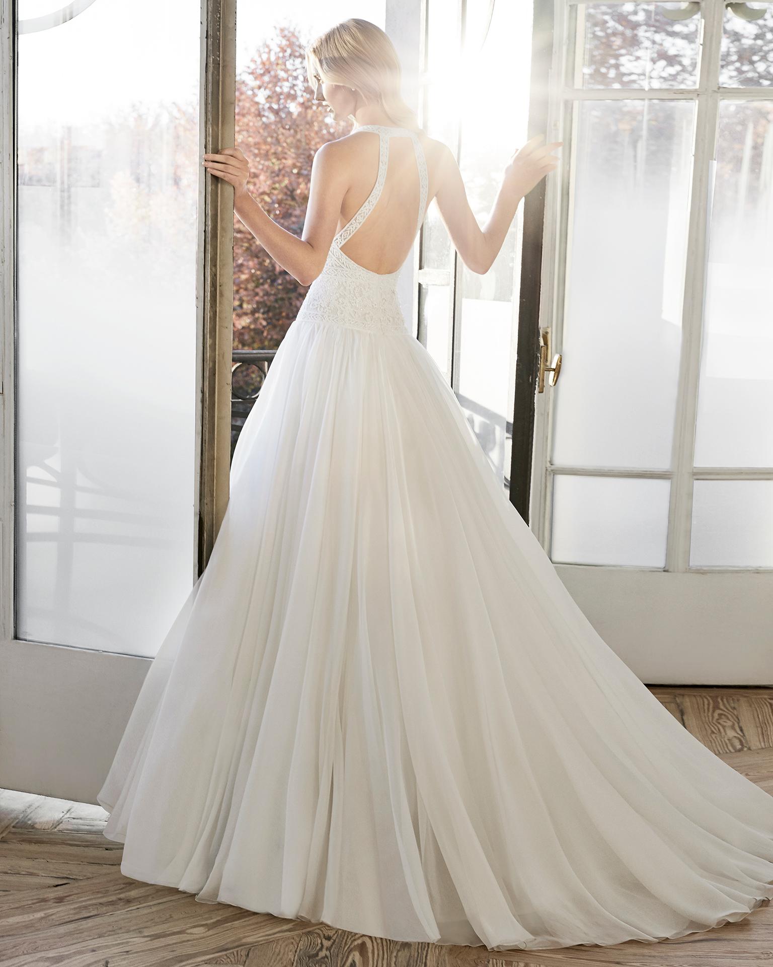 Vestido de novia estilo línea A en voile, encaje y pedrería. Escote halter y espalda descubierta. Disponible en color natural. Colección AIRE BARCELONA 2019.