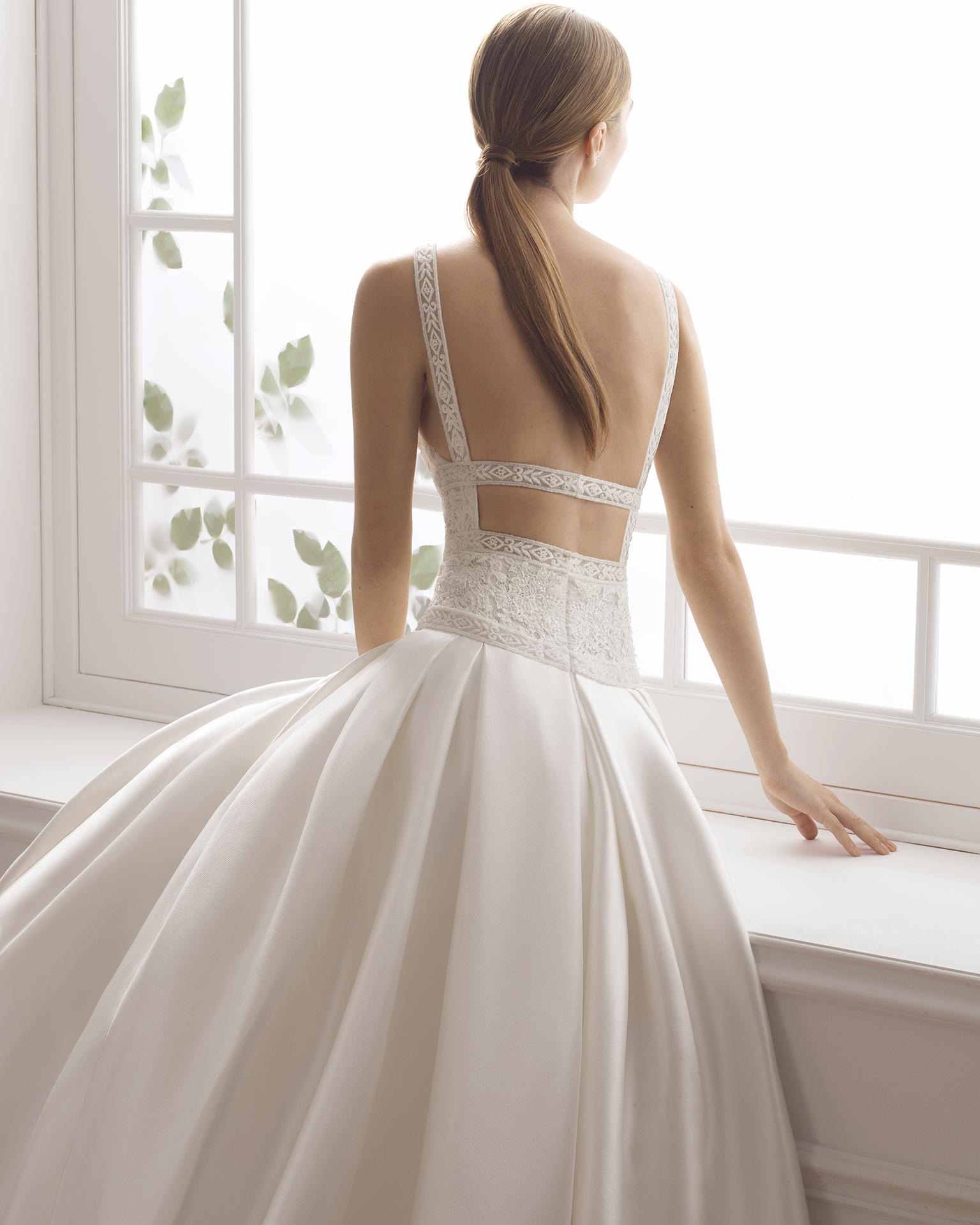 Vestido de noiva estilo clássico de tamis e renda de brilhantes. Decote à barco e costas descobertas. Disponível em cor natural. Coleção AIRE BARCELONA 2019.