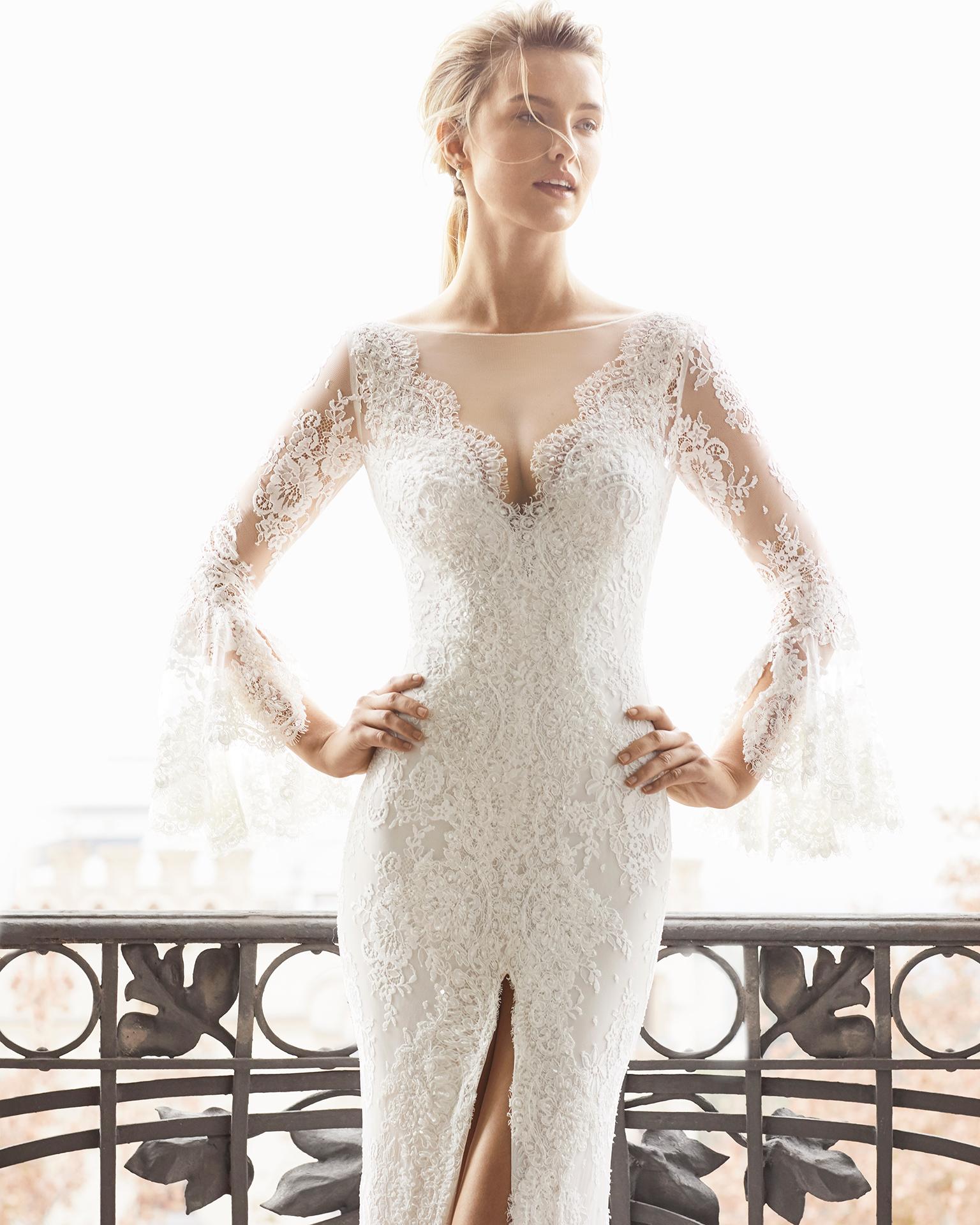 Robe de mariée style flamenco en dentelle et pierreries. Décolleté plongeant avec manches longues et décolleté dans le dos avec ouverture devant. Disponible en couleur naturelle. Collection AIRE BARCELONA 2019.