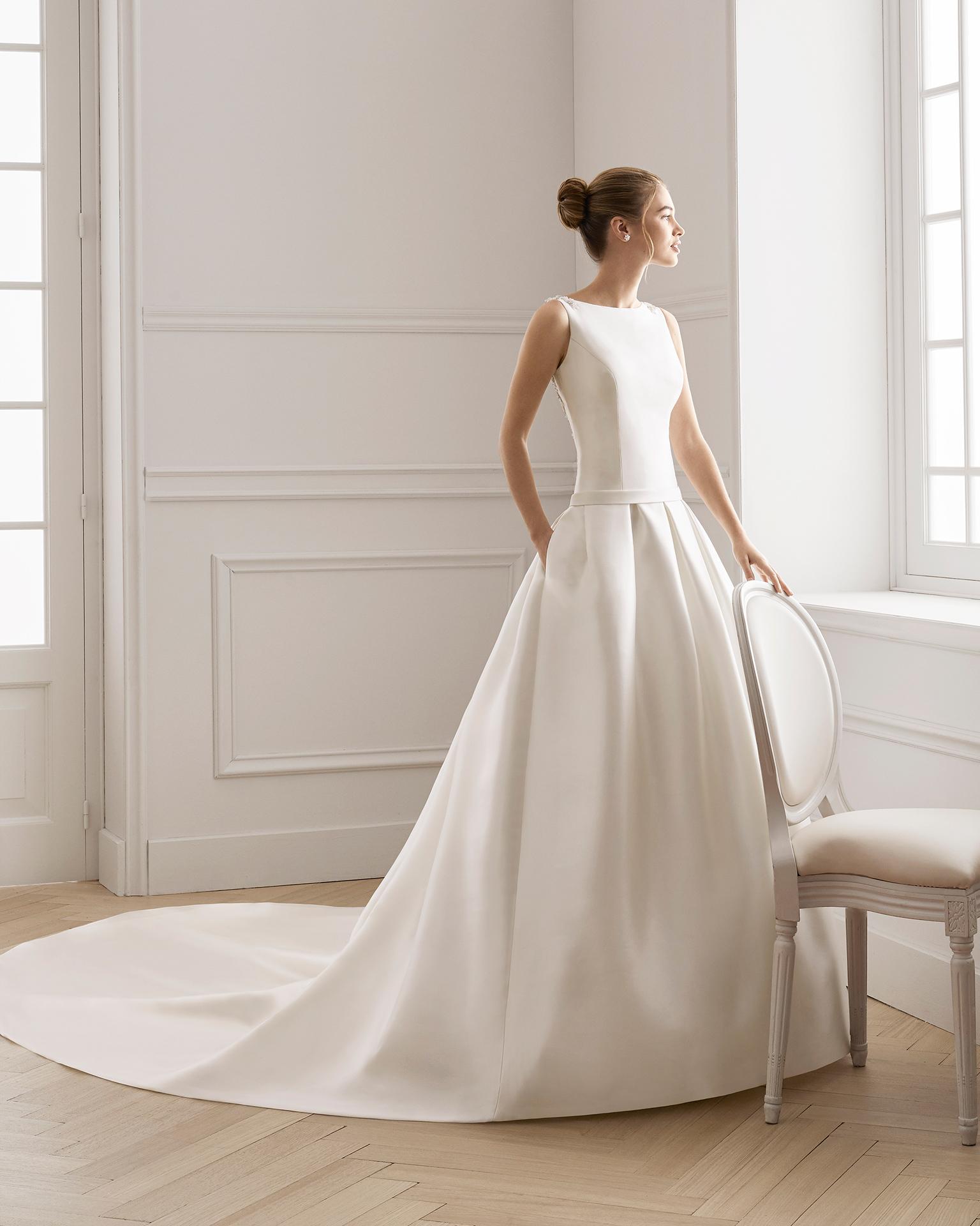 Vestido de noiva estilo clássico de tamis e renda de brilhantes. Decote à barco e costas decotadas com brilhantes. Disponível em cor natural. Coleção AIRE BARCELONA 2019.