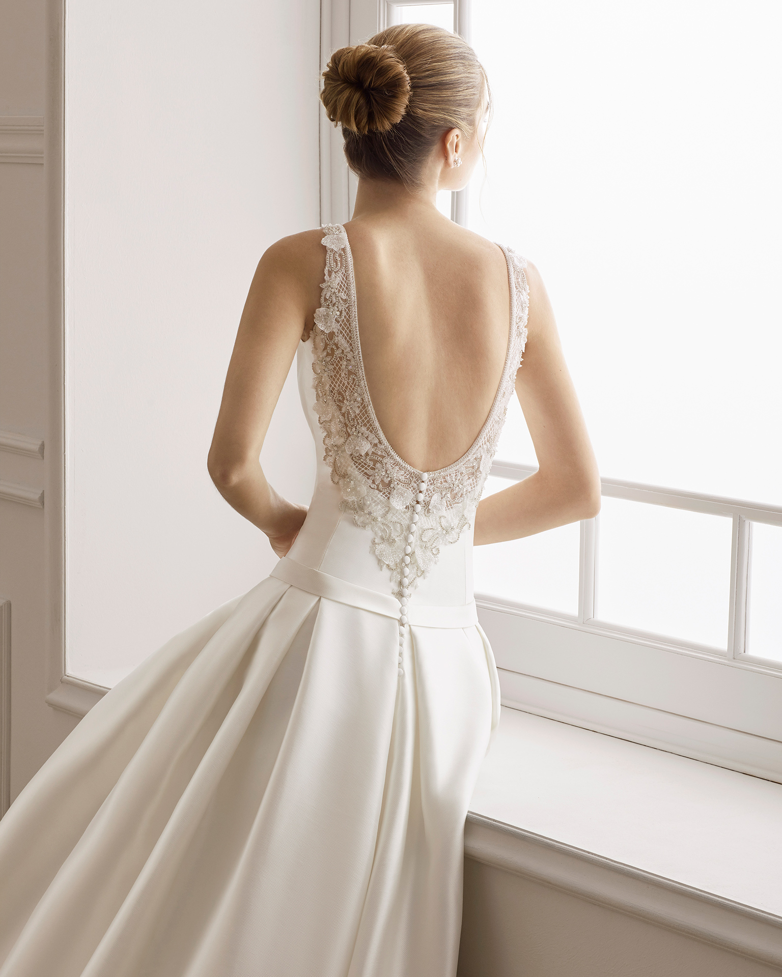 Robe de mariée style classique en tamis et dentelle avec pierreries. Col bateau et décolleté dans le dos avec pierreries. Disponible en couleur naturelle. Collection AIRE BARCELONA 2019.