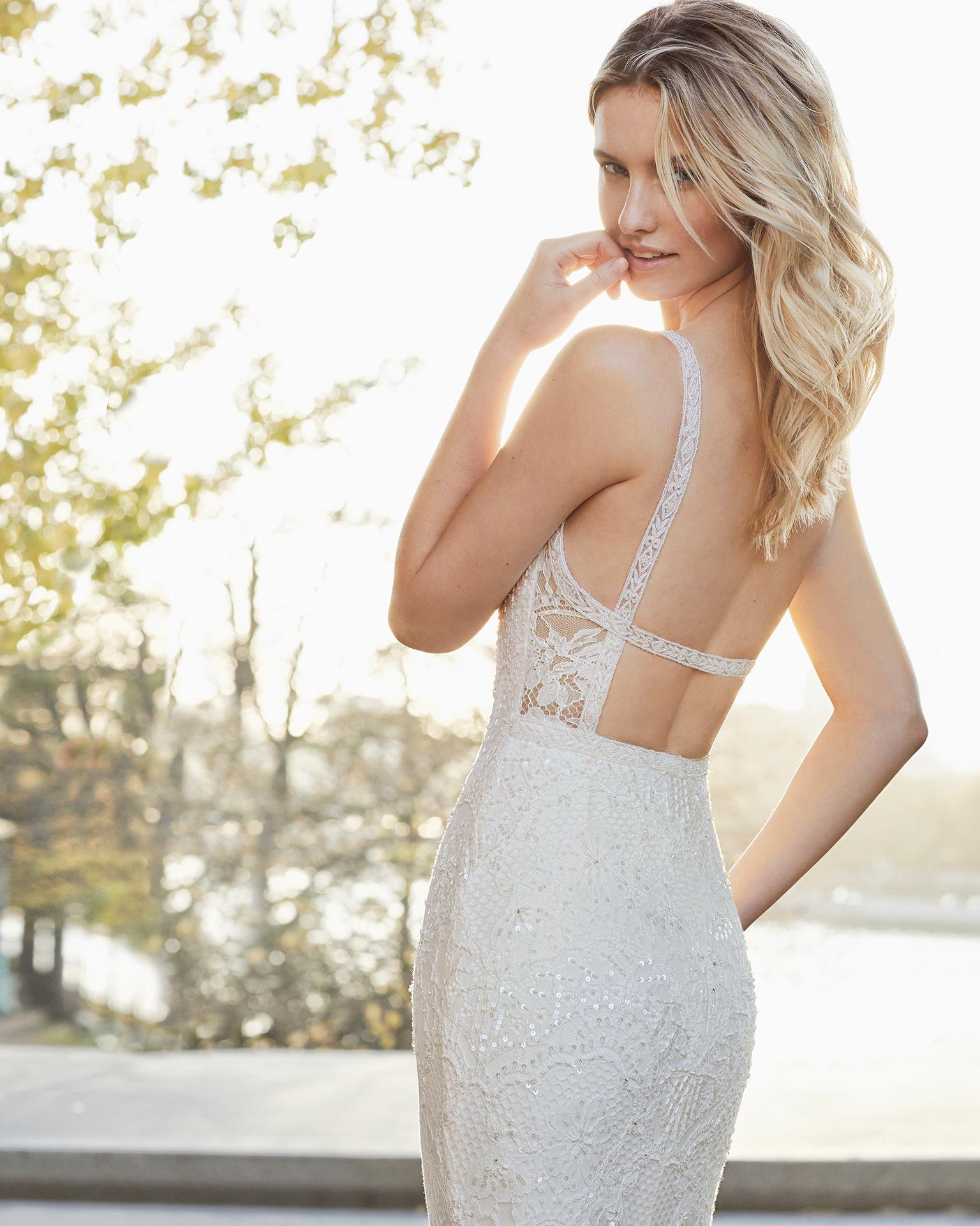 Robe de mariée coupe droite en dentelle et pierreries. Col en V avec dos nu. Disponible en couleur naturelle. Collection AIRE BARCELONA 2019.