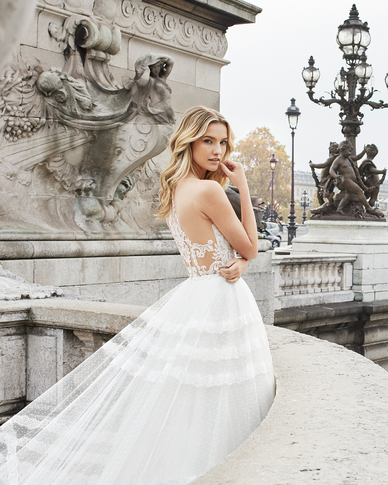 Romantic lace and tulle wedding dress. Deep-plunge neckline and lace back with sheer inserts. Available in natural. 2019 AIRE BARCELONA Collection.