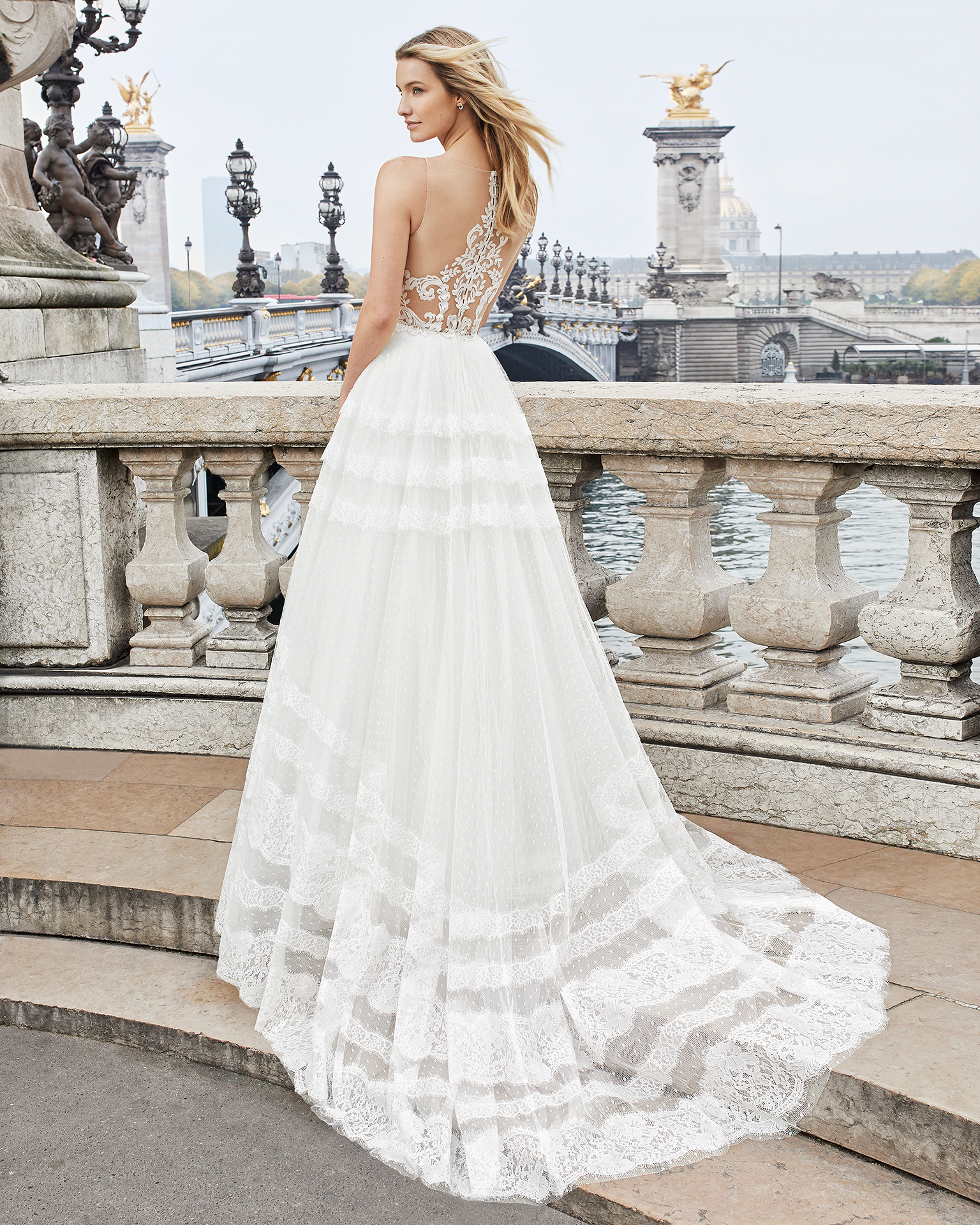 Robe de mariée style romantique en dentelle et tulle. Décolleté plongeant et dos en dentelle avec transparences. Disponible en couleur naturelle. Collection AIRE BARCELONA 2019.